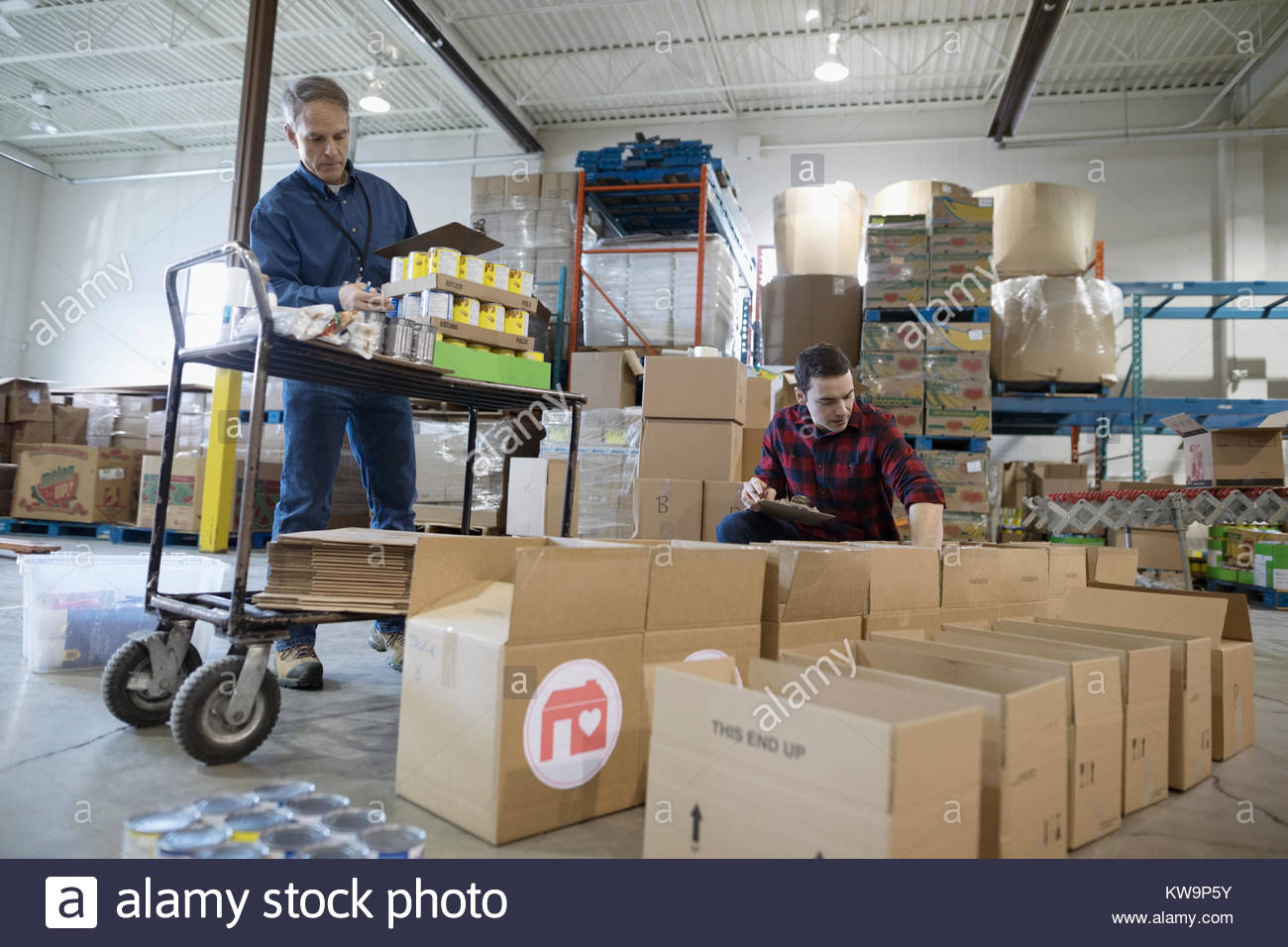 Male volunteers with canned food filling donation boxes in warehouse - Stock Image