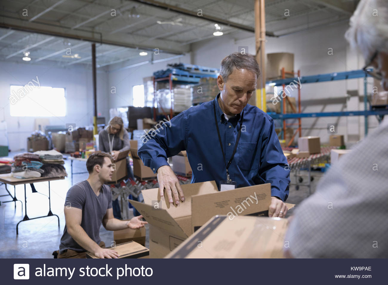 Male volunteer packing box for food drive in warehouse - Stock Image