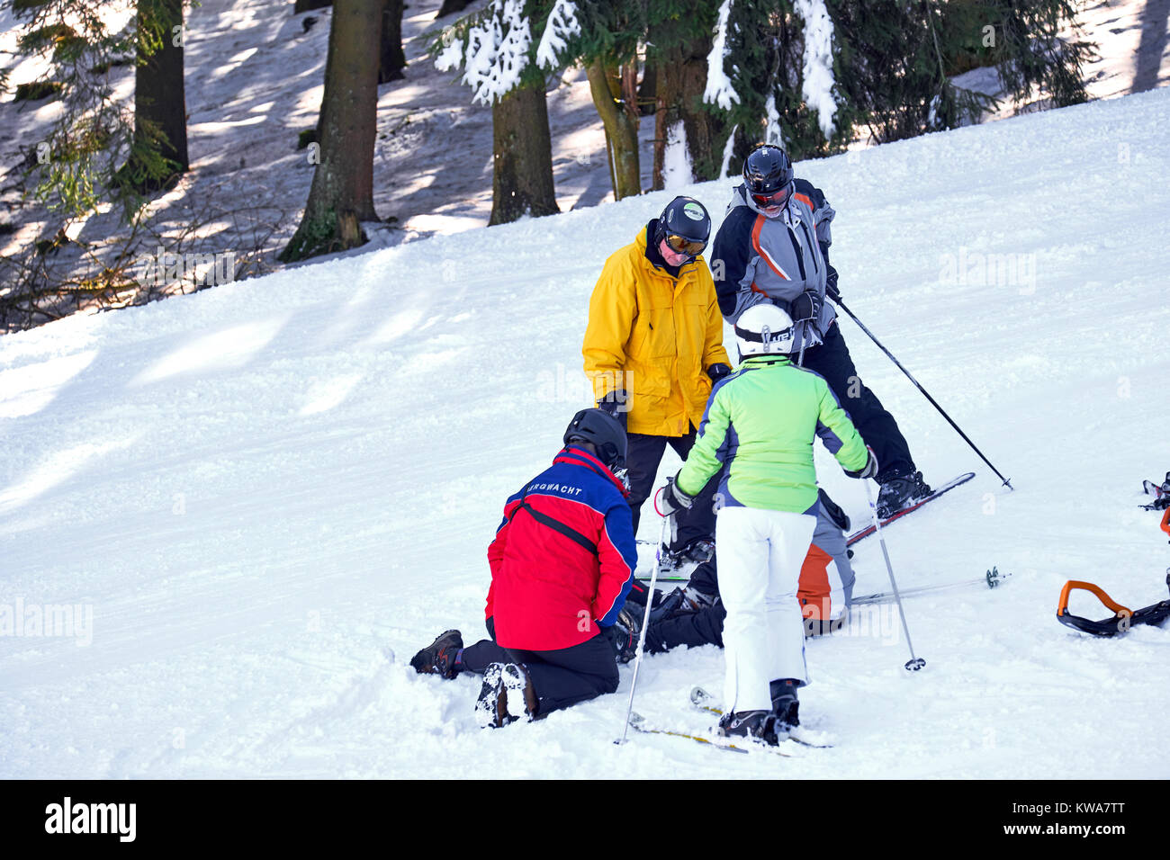 WINTERBERG, GERMANY - FEBRUARY 15, 2017: Rescue team looking at a woman's leg at on a ski slope at Winterberg - Stock Image