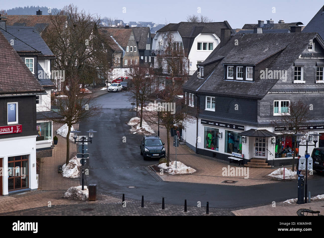 WINTERBERG, GERMANY - FEBRUARY 16, 2017: Narrow street in Winterberg with slate decorated town villas on both sides - Stock Image