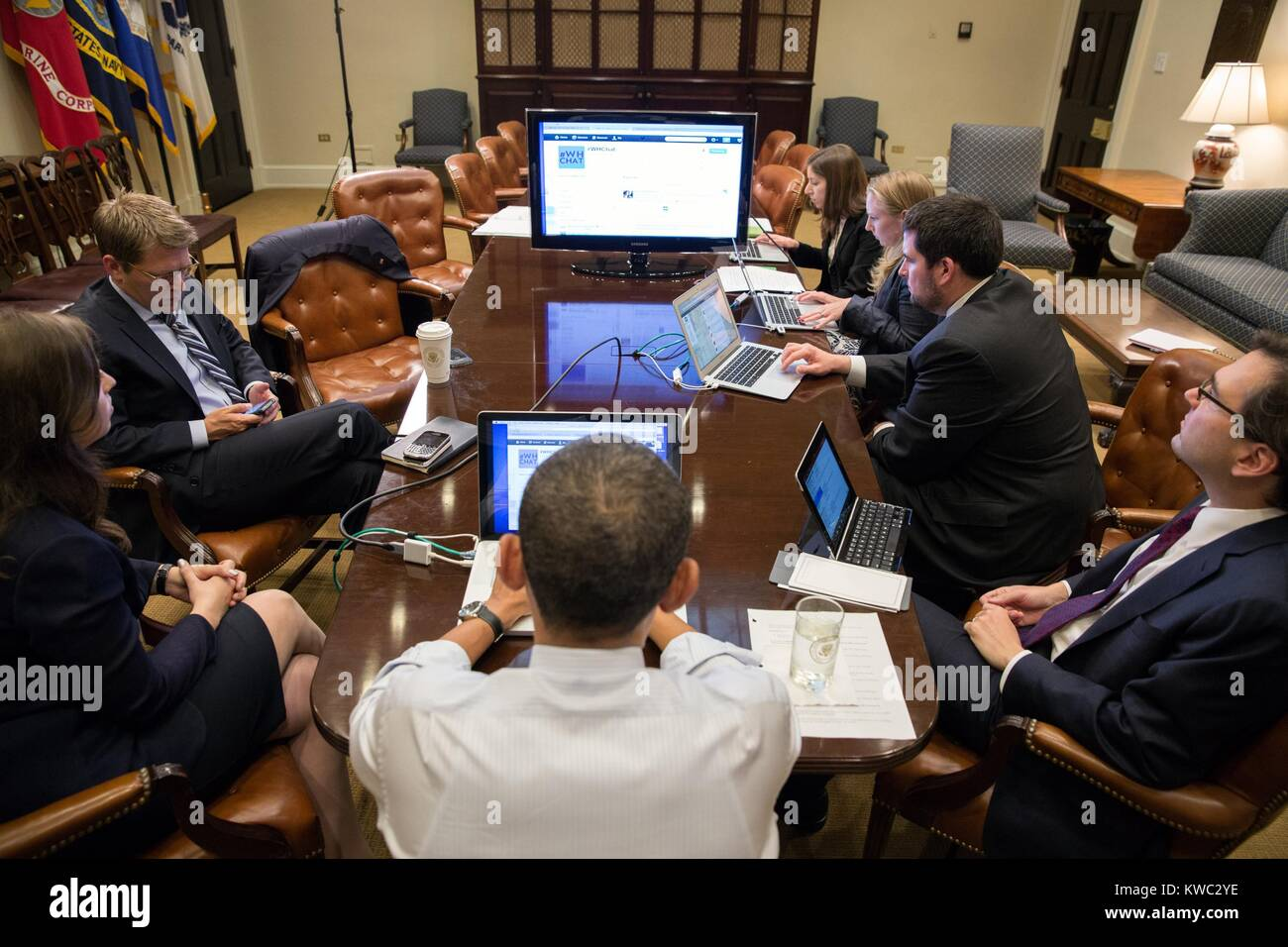President Barack Obama (center, back to camera) in a live Twitter question and answer session. Roosevelt Room of - Stock Image