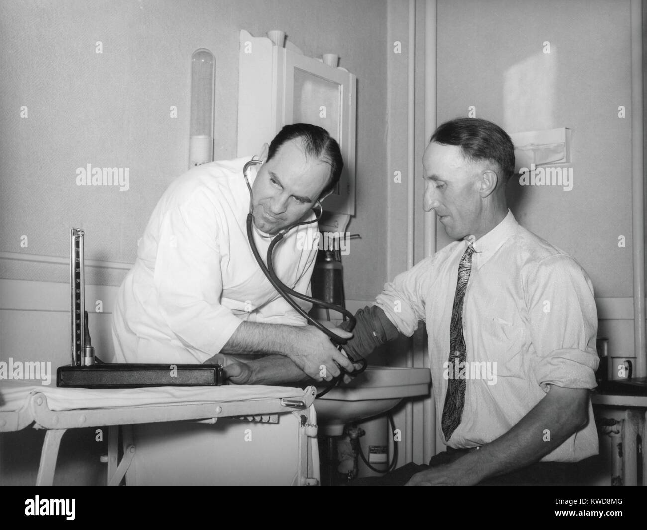 Doctor at a medical cooperative taking blood pressure of a patient in Box Elder County, Utah, 1940. In Northwest - Stock Image