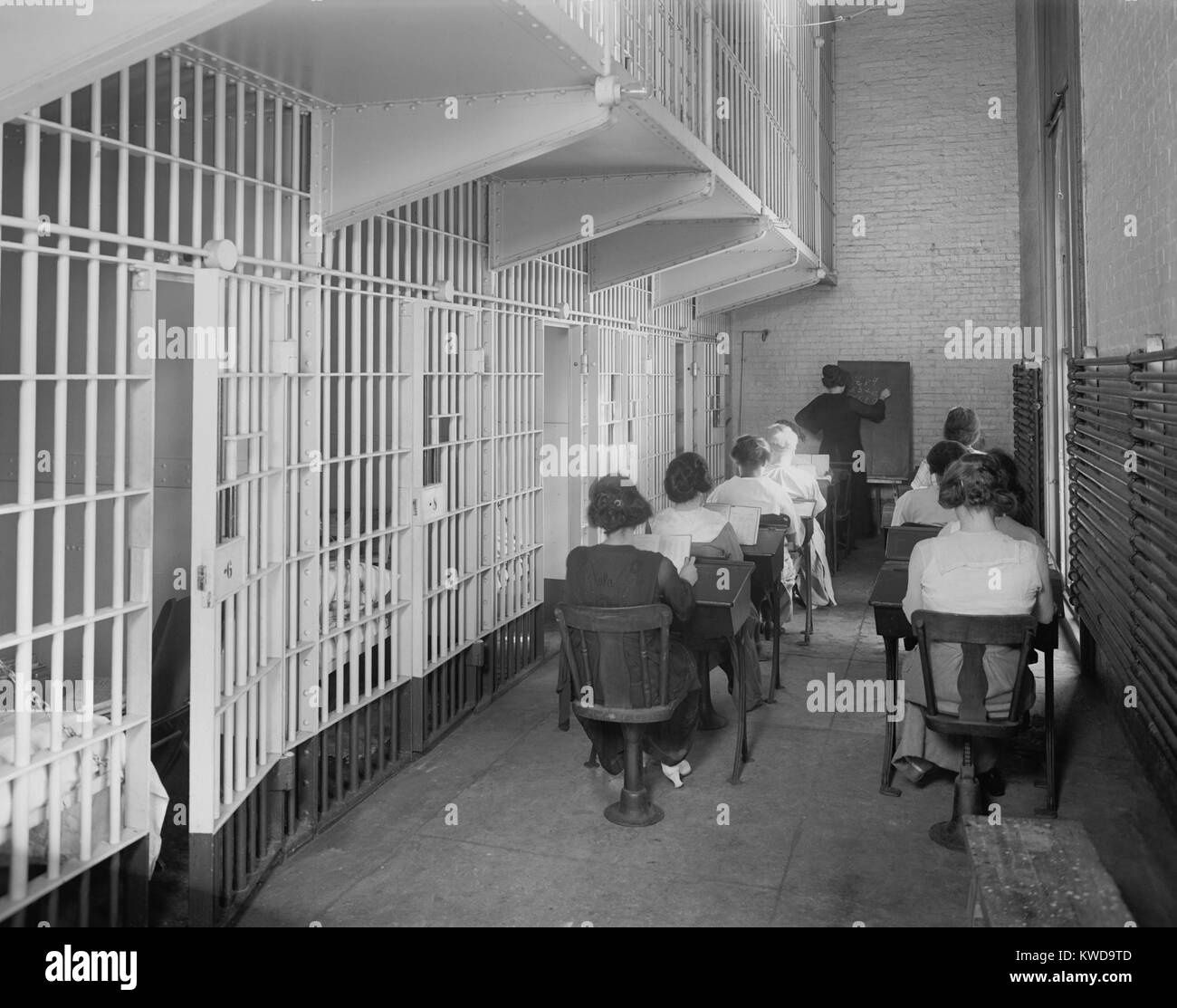 Young women at desks in an American jail c. 1920. Dressed in street clothing, they sit in two rows of desks in a - Stock Image