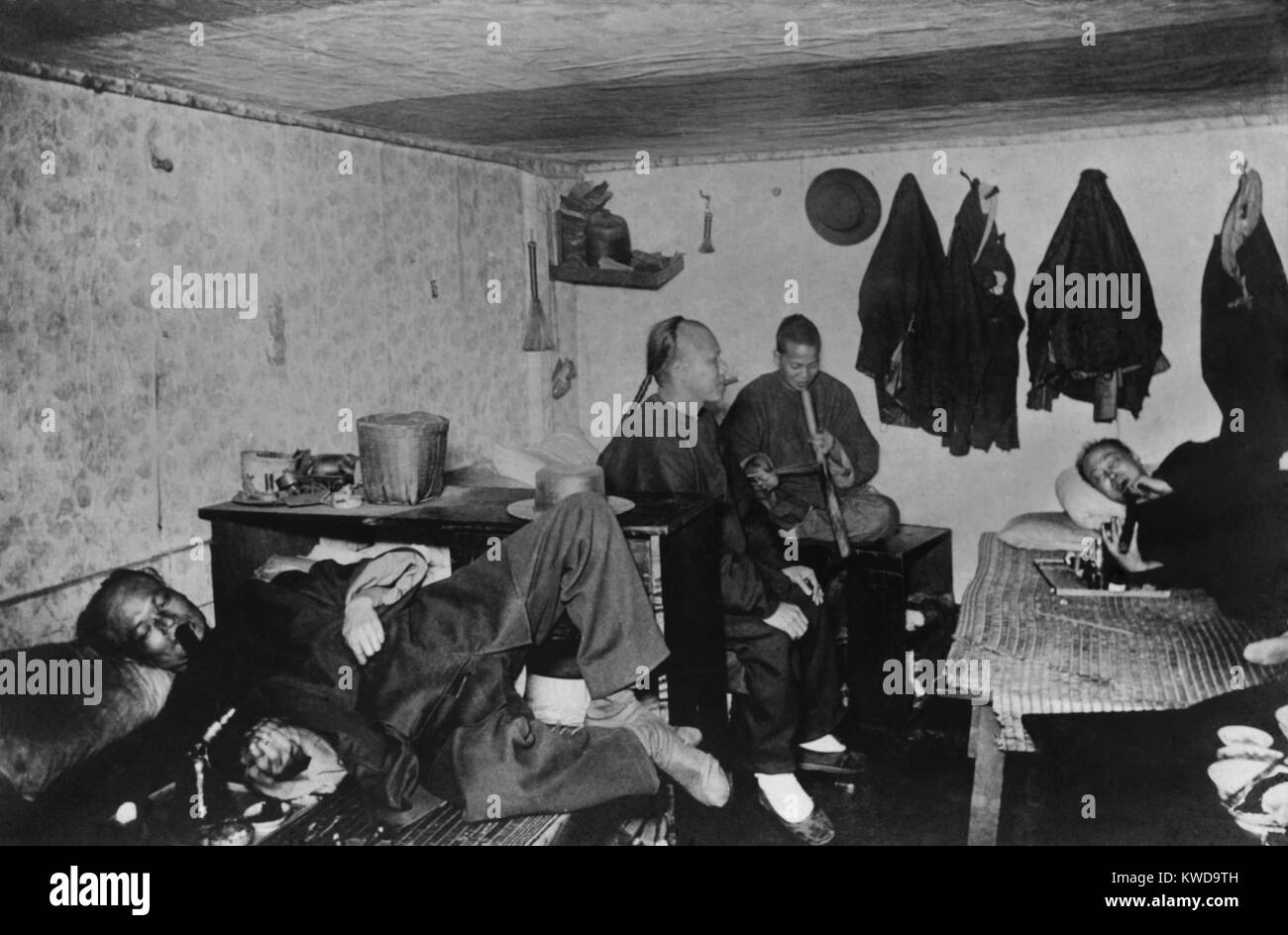 Four Chinese men smoking opium in a lodging house in San Francisco's Chinatown, c. 1905 (BSLOC_2016_10_74) - Stock Image