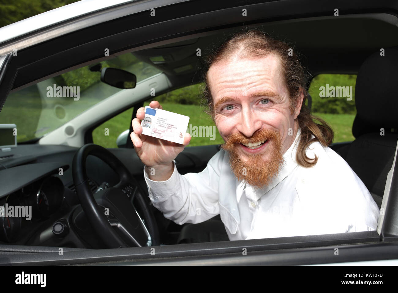driver smiling sitting in car and showing drivers license - Stock Image