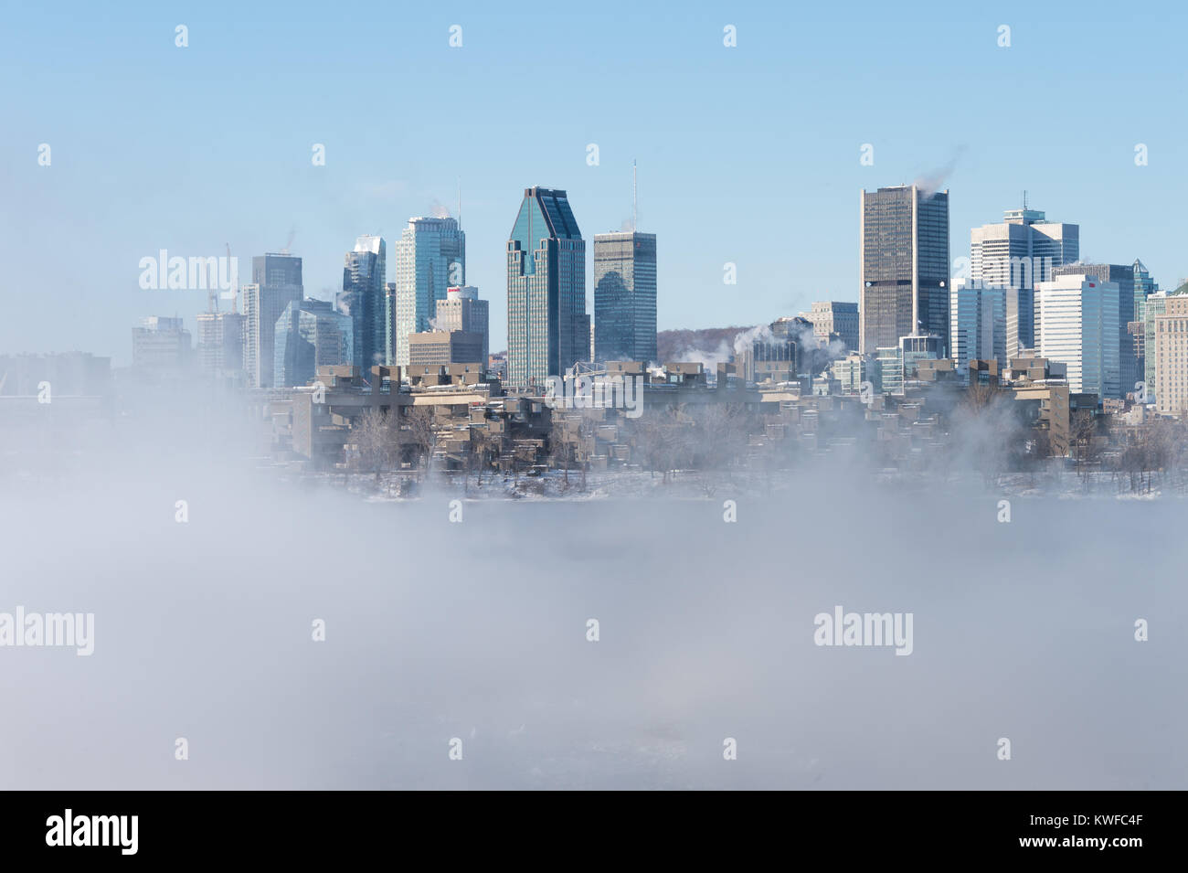 Montreal, CA - 1 January 2018: Montreal Skyline in winter as ice fog rises off the St. Lawrence River - Stock Image
