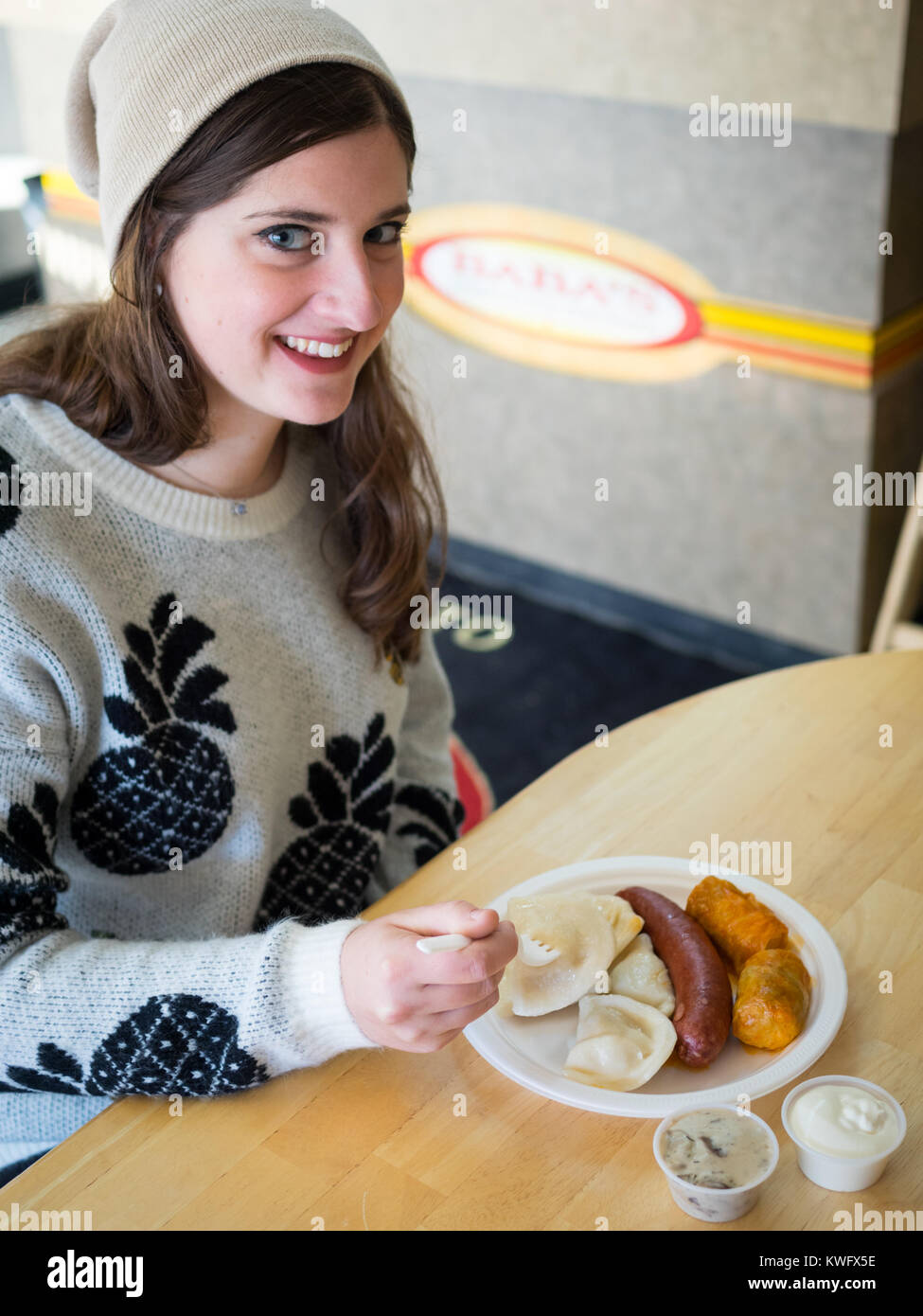 A pretty brunette girl enjoys a platter of perogies, cabbage rolls, and a smokie from Baba's Homestyle Perogies - Stock Image