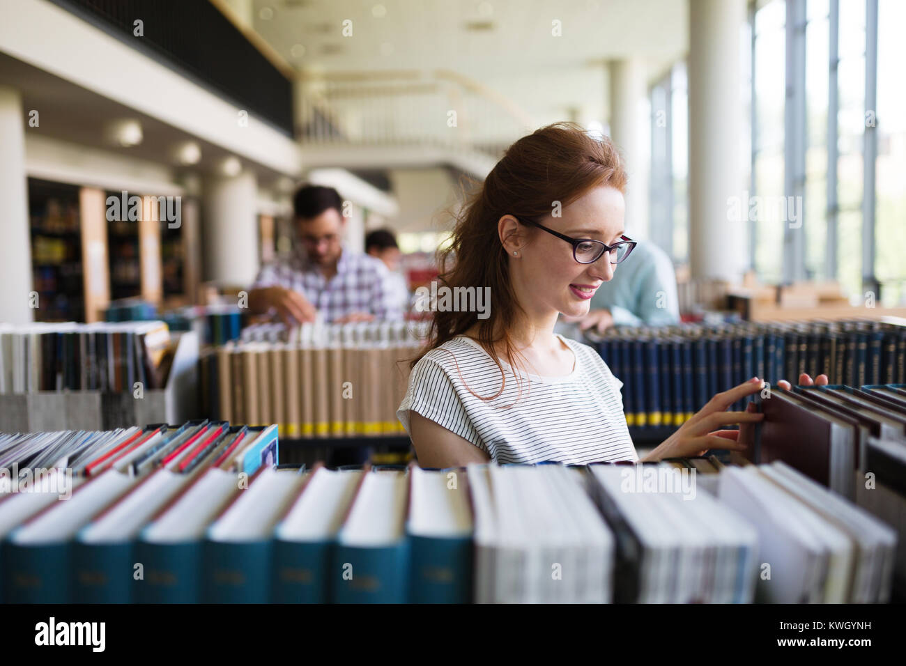 Portrait of a pretty smiling girl reading book in library - Stock Image
