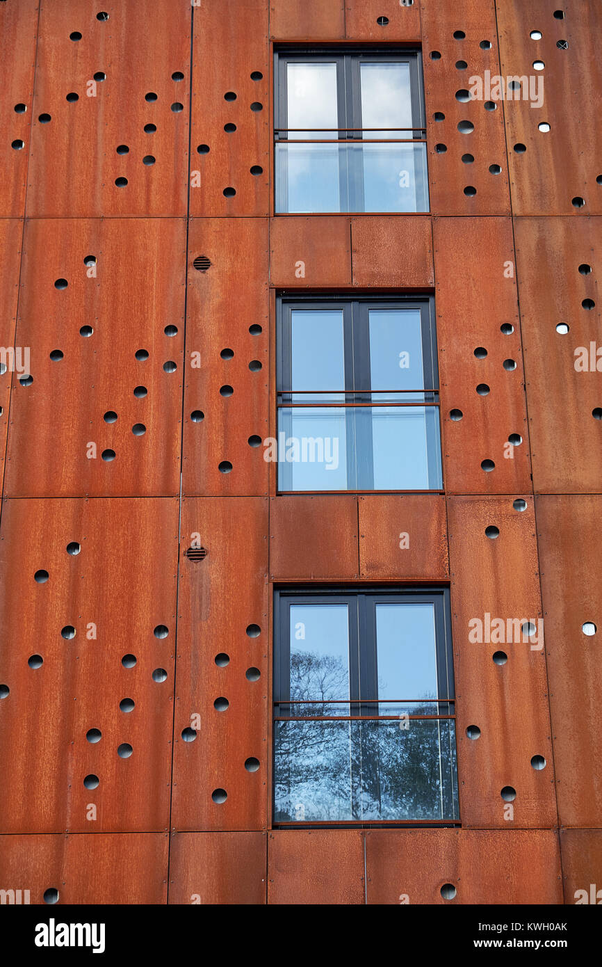 Closeup of windows with french balconys in building facade with rusty metal plates with round holes - Stock Image