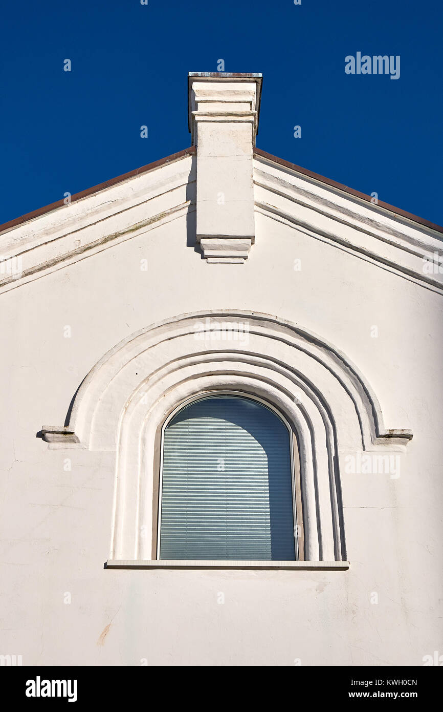 Arched window in a plastered triangled gable with a chimney rising against a blue sky - Stock Image
