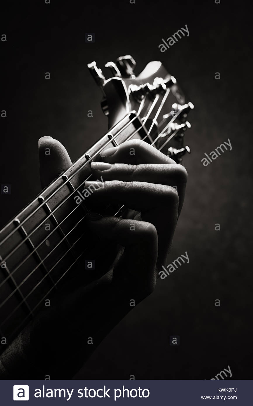 Hand of a Guitarist close-up with only neck and head of guitar in image - Stock Image