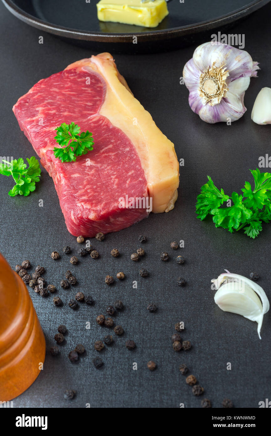 Beef sirloin steak. Fresh with garlic, black pepper and parsley. - Stock Image