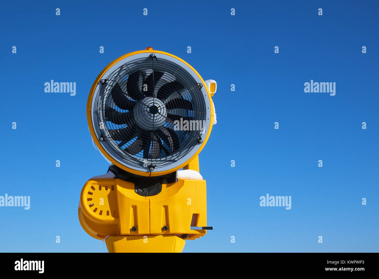 One turned off yellow snow cannon at Ski Carousel Winterberg against a clear blue sky - Stock Image