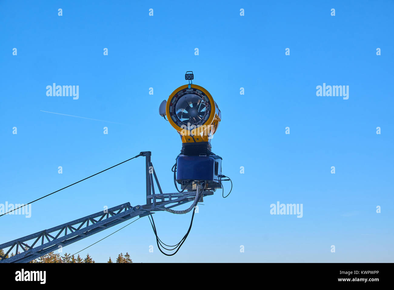 Turned off yellow snow cannon hanging in the air over a piste at Ski Carousel Winterberg against a clear blue sky - Stock Image