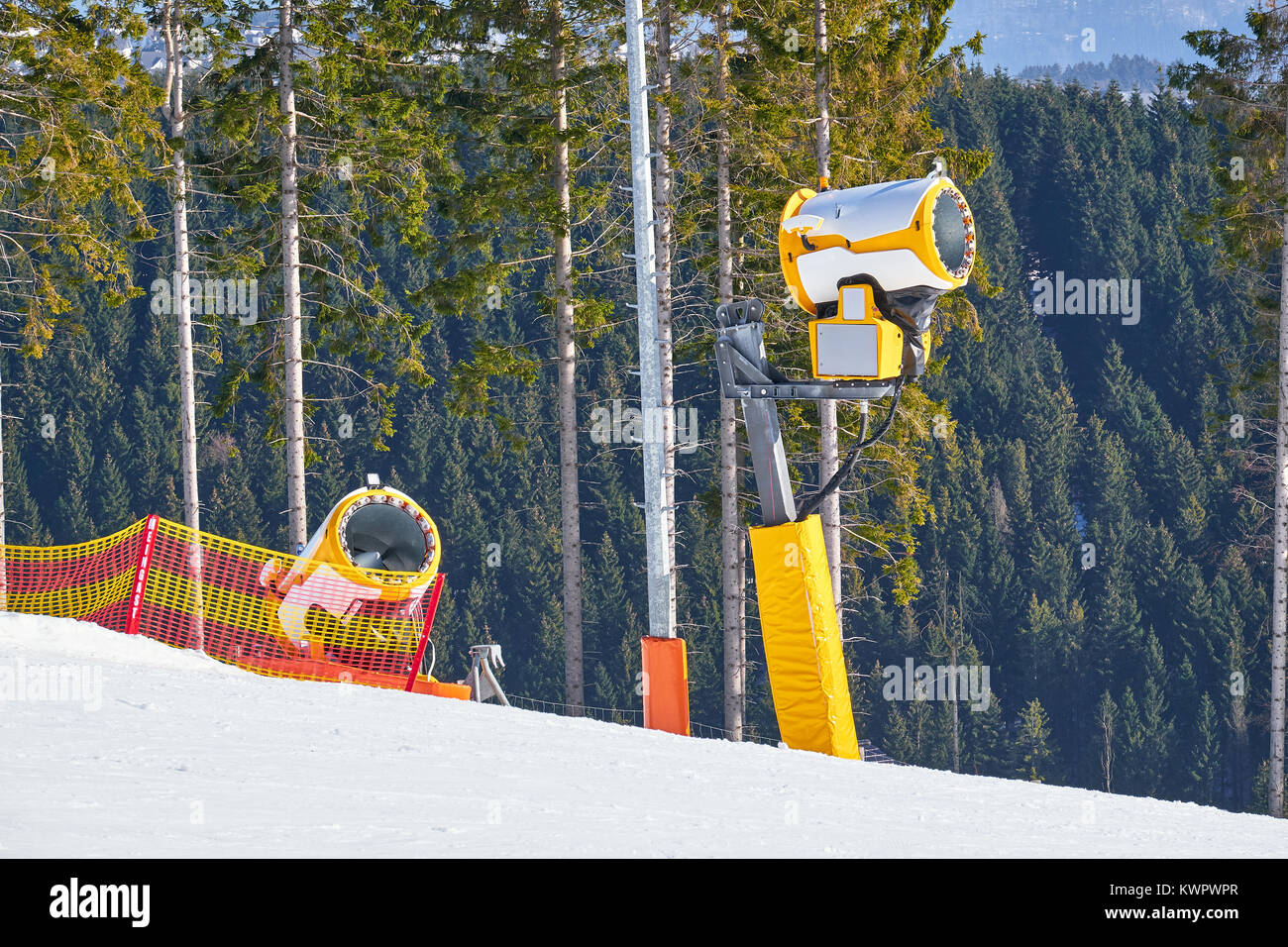 Two turned off yellow snow cannons on a piste at Ski Carousel Winterberg with pine forest in the background - Stock Image