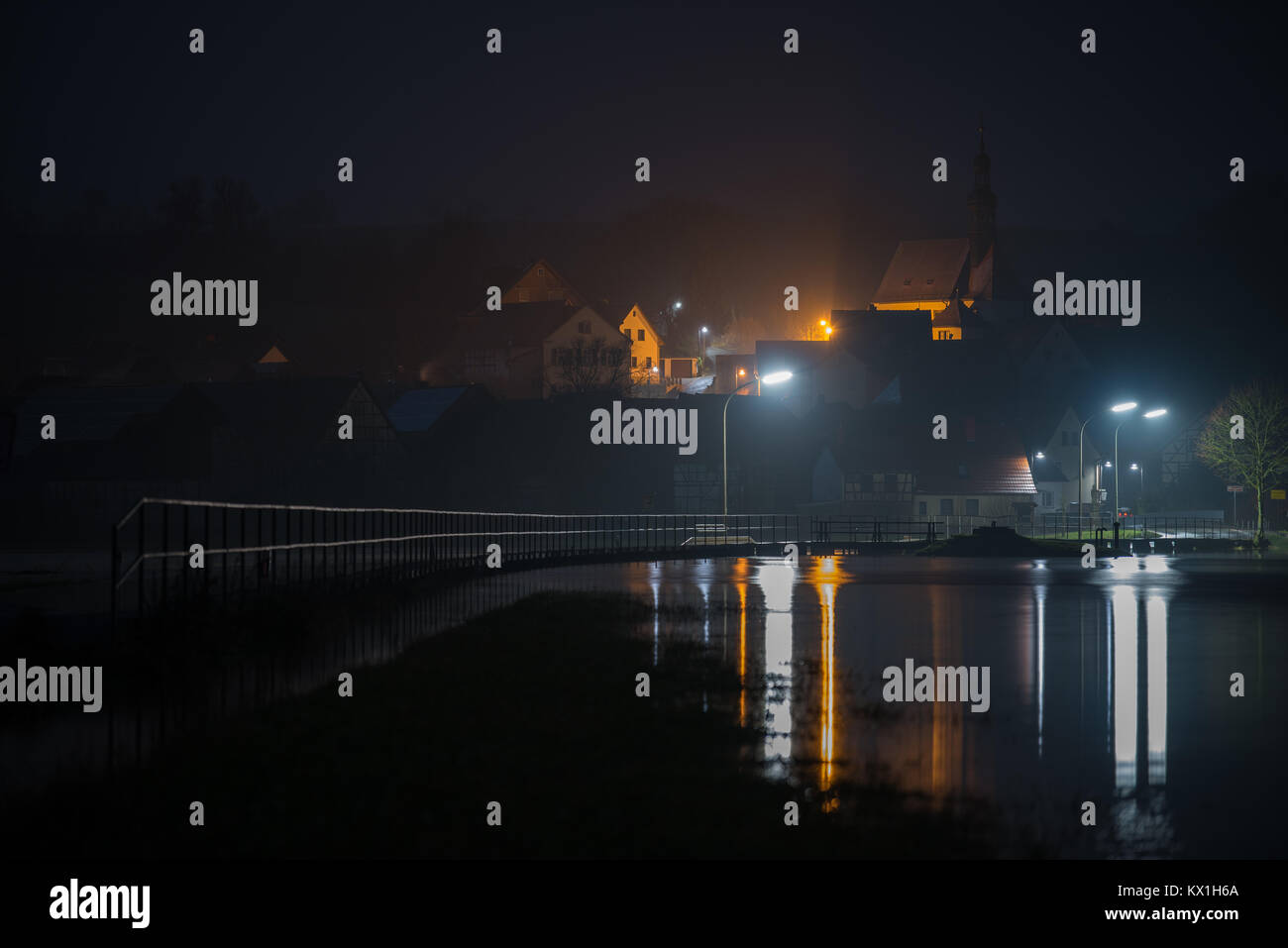 Gleusdorf, Germany. 6th Jan, 2018. The floodwater of the river Itz overflows the river banks flooding a nearby road - Stock Image