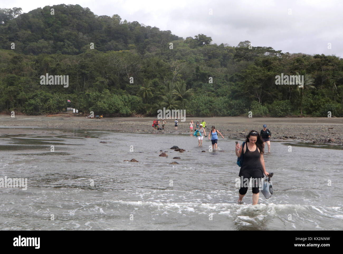 Tourist wading in ocean to boat Stock Photo