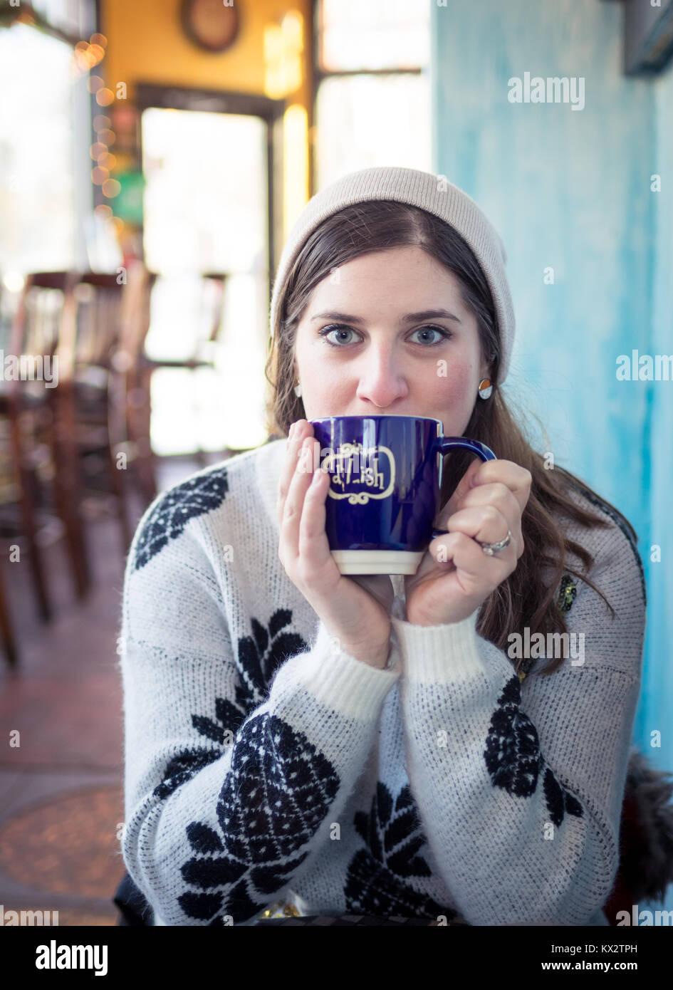 A pretty brunette girl sips a caffè latte from d'Lish by Tish Cafe in Saskatoon, Saskatchewan, Canada. - Stock Image