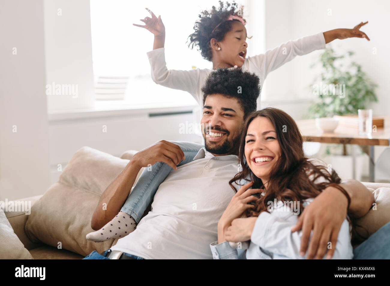 Family lifestyle portrait of a mum and dad with their kid - Stock Image