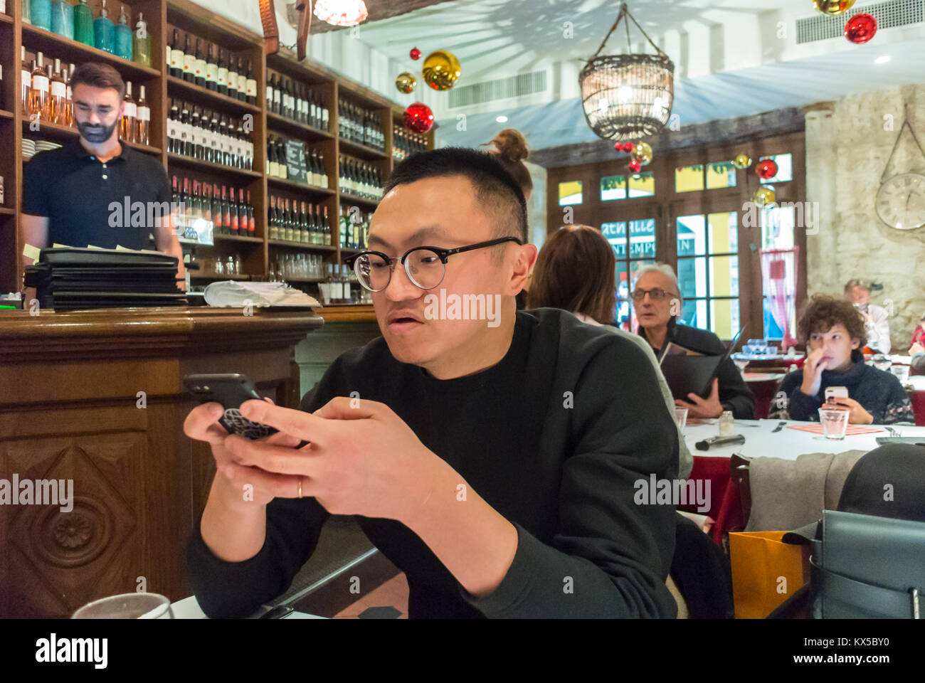 Nice, France, Chinese Man using Smart Phone at Table in Local Restaurant, - Stock Image