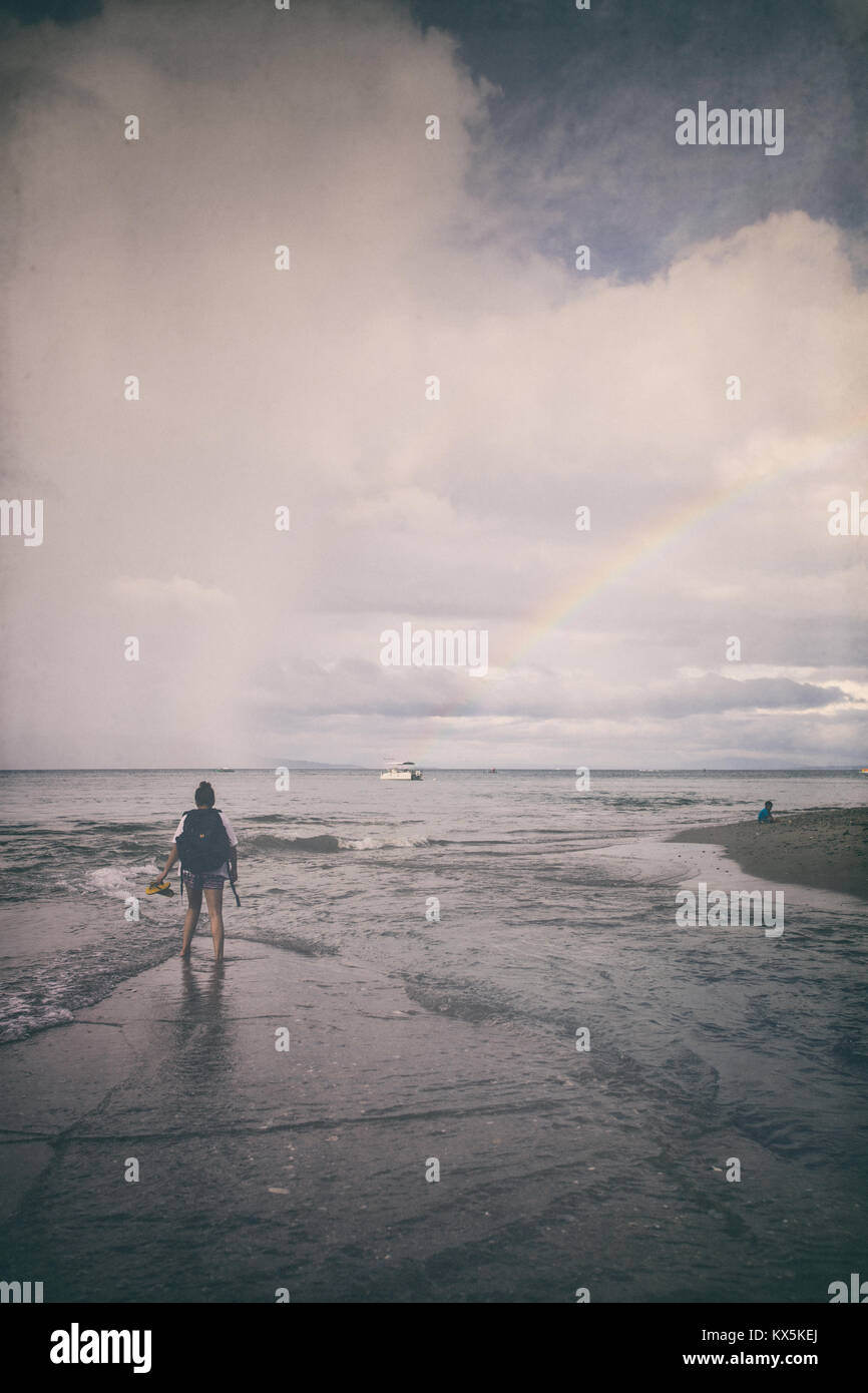 Girl walking on the shore, dramatic sky - Stock Image