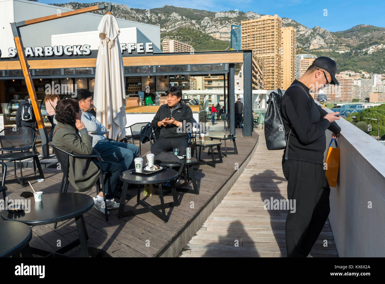 Monaco, Monte Carlo, Chinese Tourists sharing Drinks at Starbuck's Cafe Restaurant Terrace Sidewalk near Sea - Stock Image