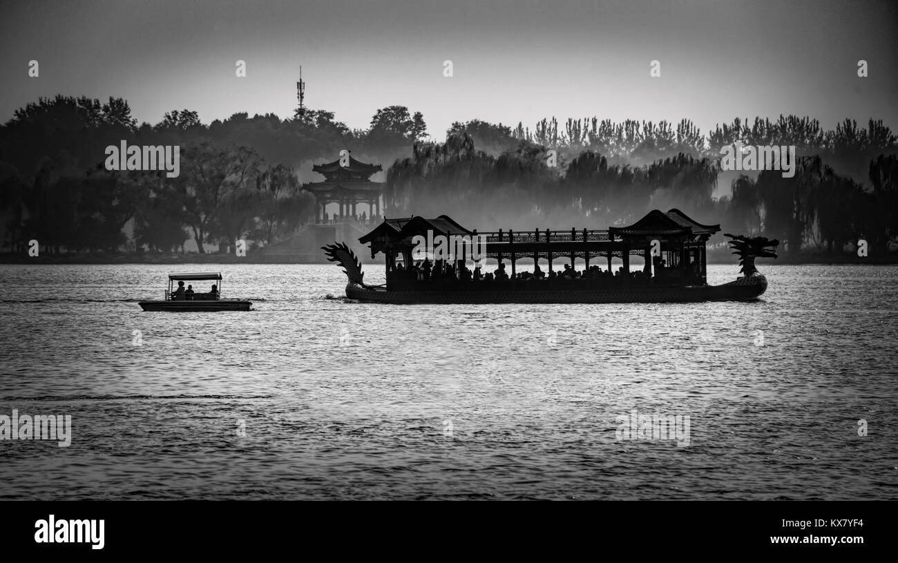 Silhouettes of a dragon boat and small boat on Kunming Lake on the grounds of the Summer Palace in Beijing, China - Stock Image