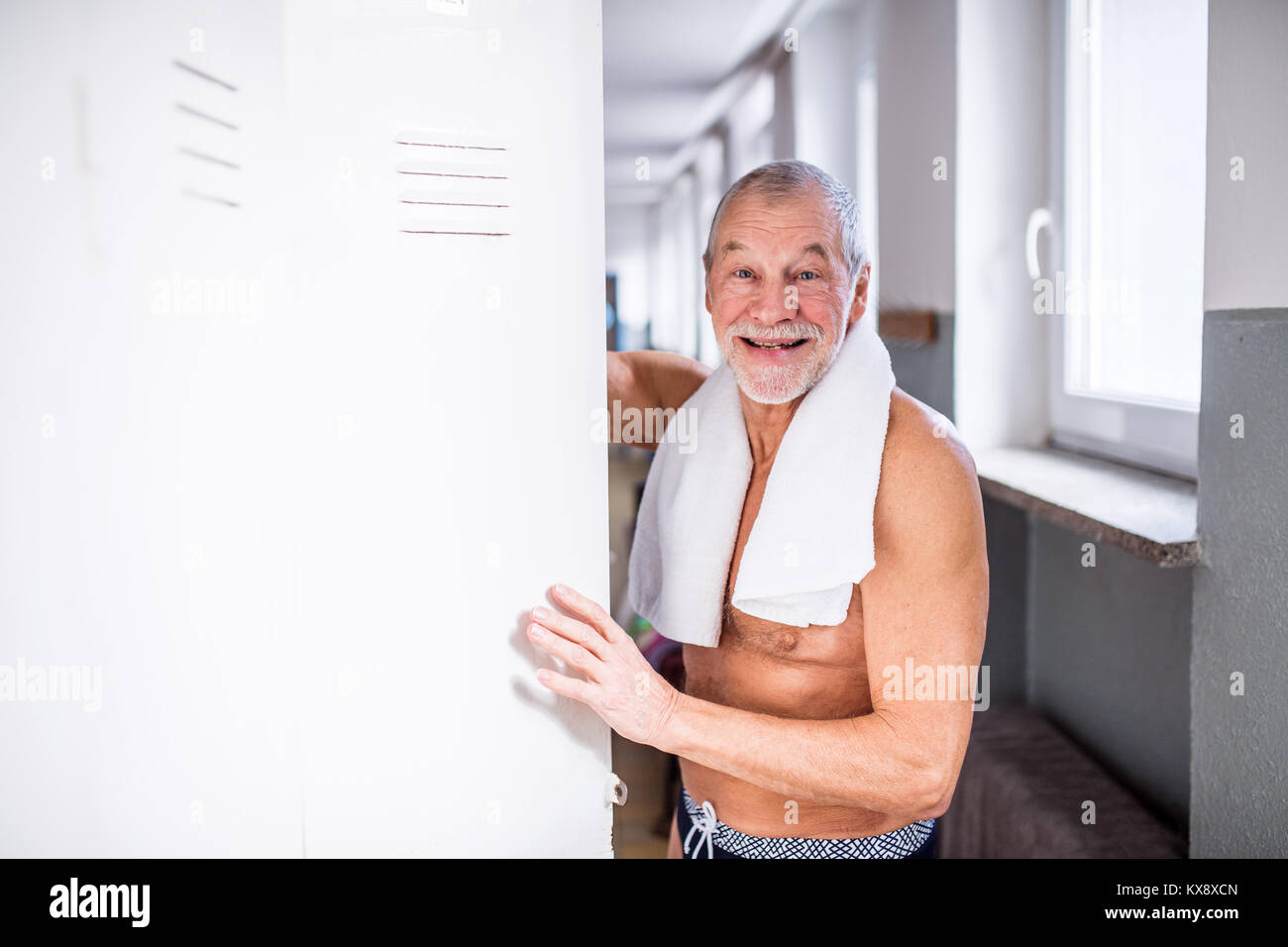 Senior man standing by the lockers in an indoor swimming pool. - Stock Image