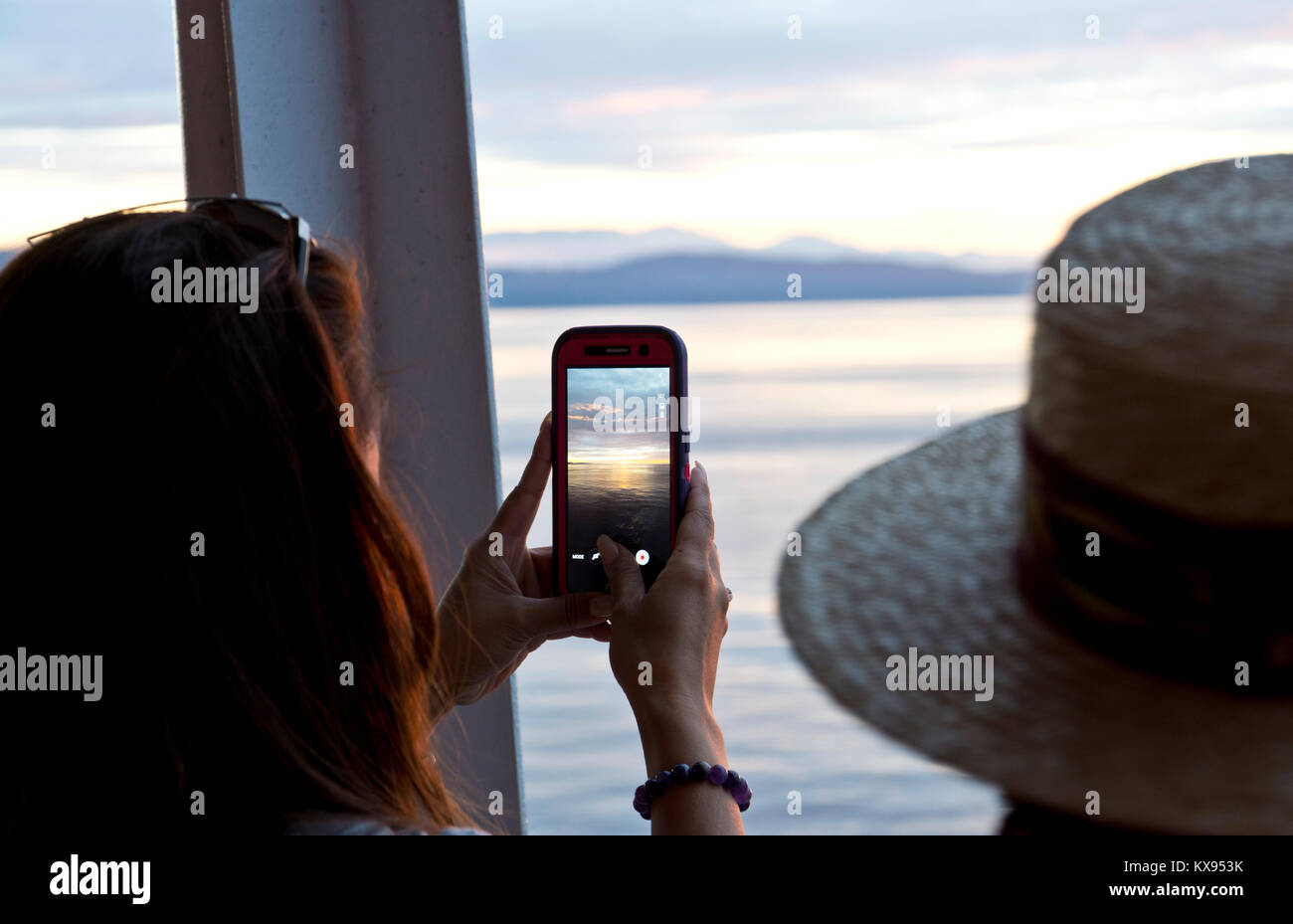Woman taking a photograph with her cell phone of the sunset on the water.  On a BC Ferry on the Strait of Georgia. Stock Photo