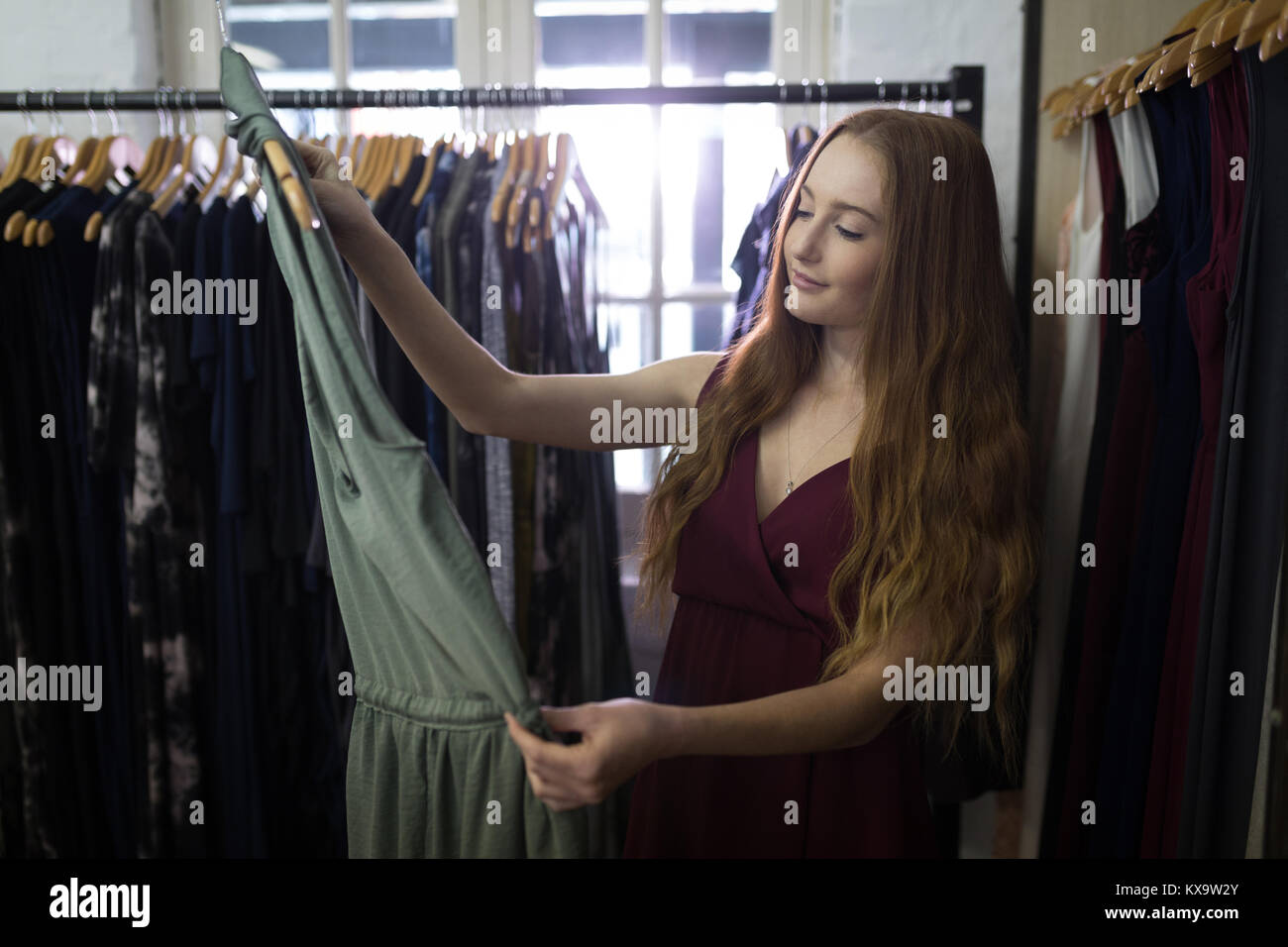 Young woman selecting a dress - Stock Image