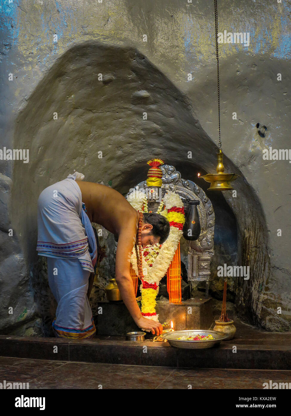 A Hindu devotee makes an offering to the Hanuman, a popular deity in Hinduism, at the Batu Caves in Gombak, Selangor, - Stock Image