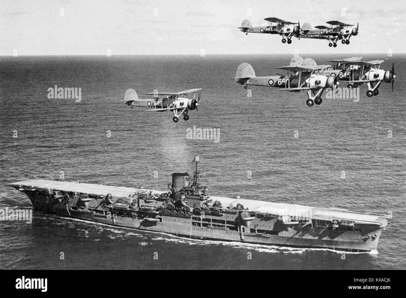 The aircraft carrier HMS Ark Royal with a flight of Swordfish overhead - Stock Image