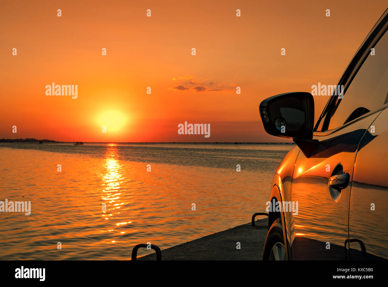 Blue compact SUV car with sport and modern design parked on concrete road by the sea at sunset. Environmentally - Stock Image