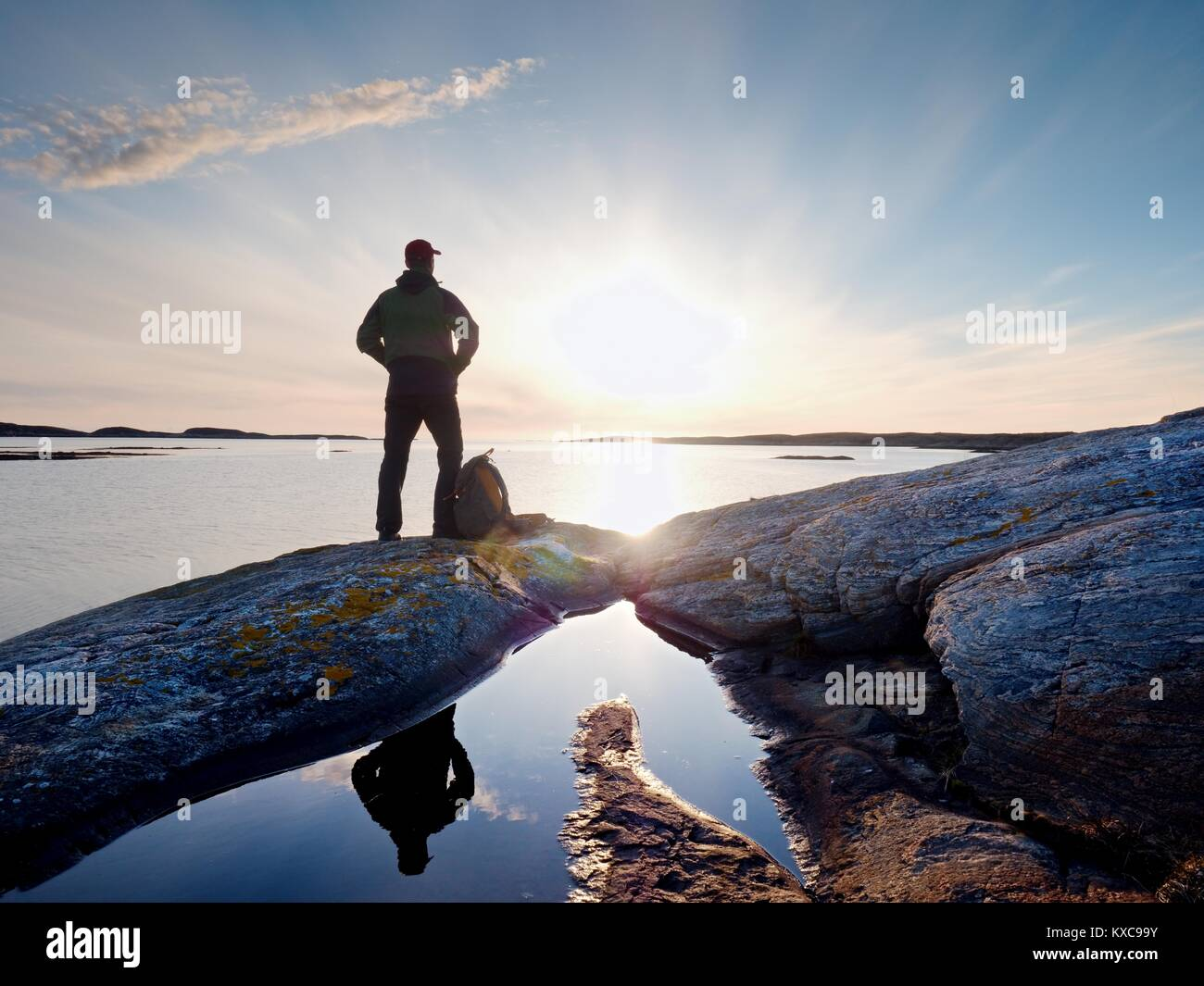 Young standing man with backpack. Hiker on the stone on the seashore at colorful sunset sky. Beautiful landscape - Stock Image
