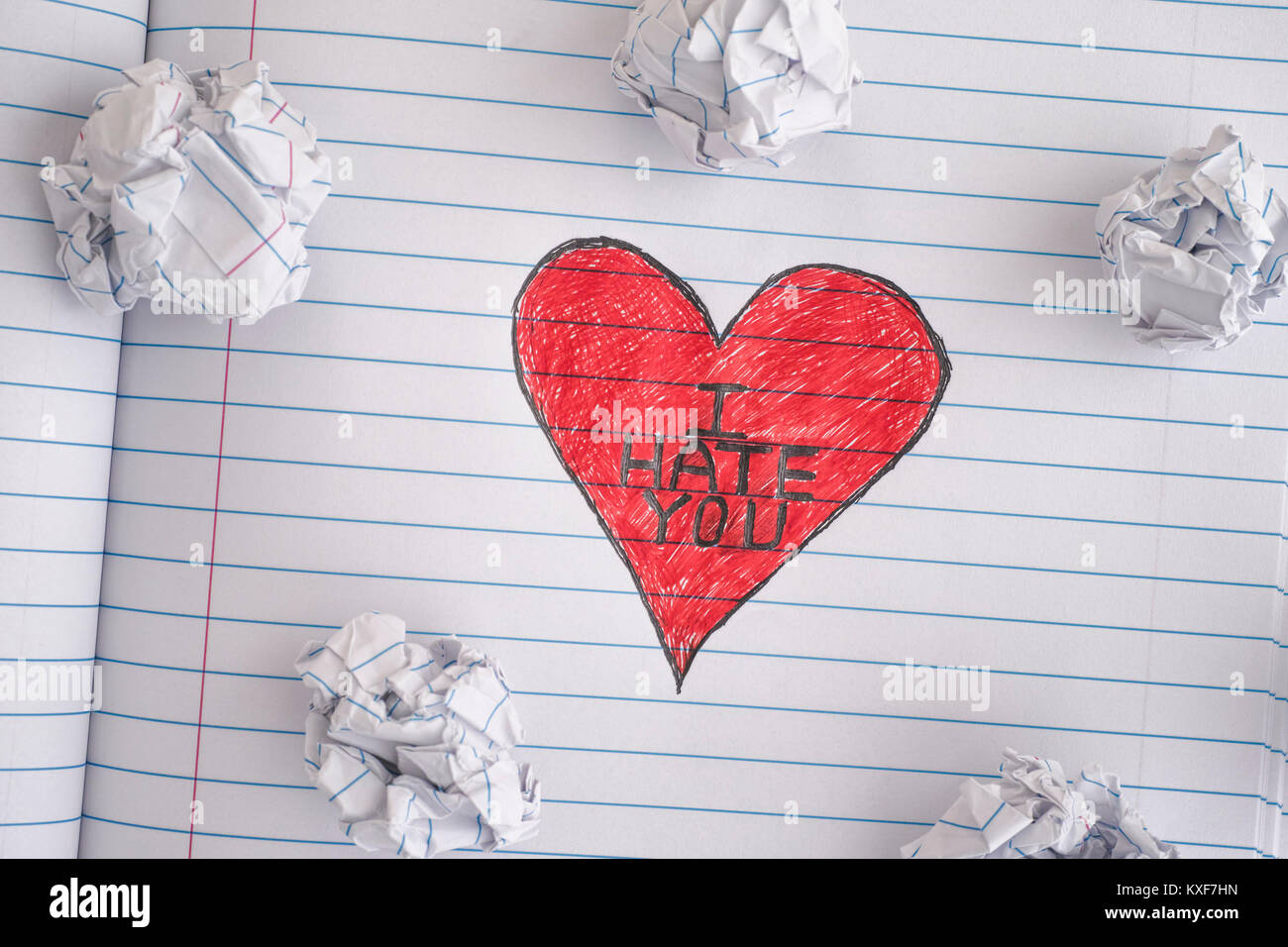 I Hate You. Red Heart with phrase I Hate You on notebook sheet with some crumpled paper balls on it. Close up. - Stock Image