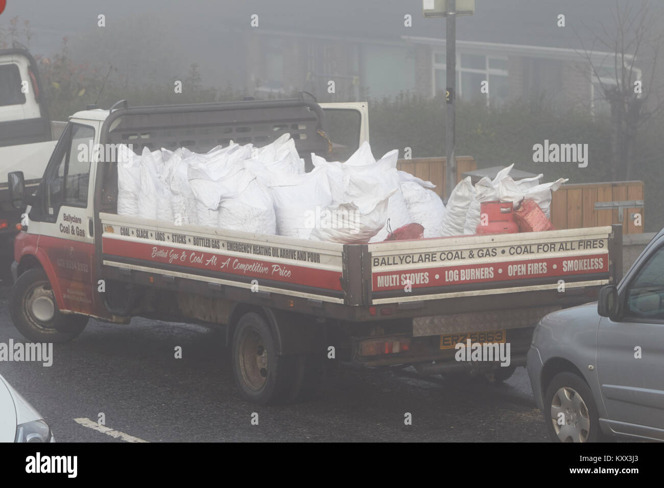 van delivering coal and solid fuel on a foggy day in the uk - Stock Image