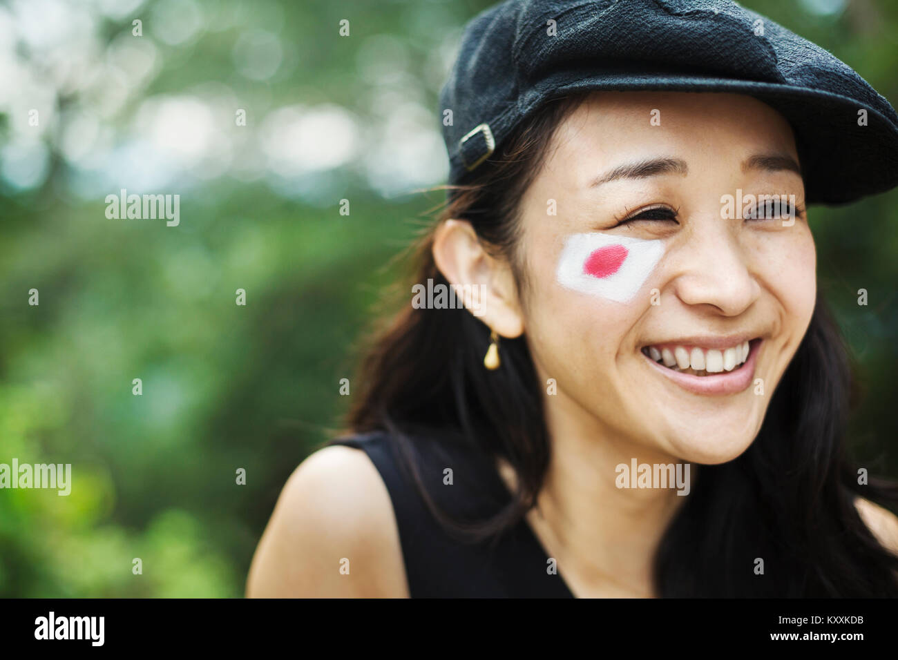 3c90f5c30ba65 Portrait of smiling young woman with black hair wearing flat cap ...