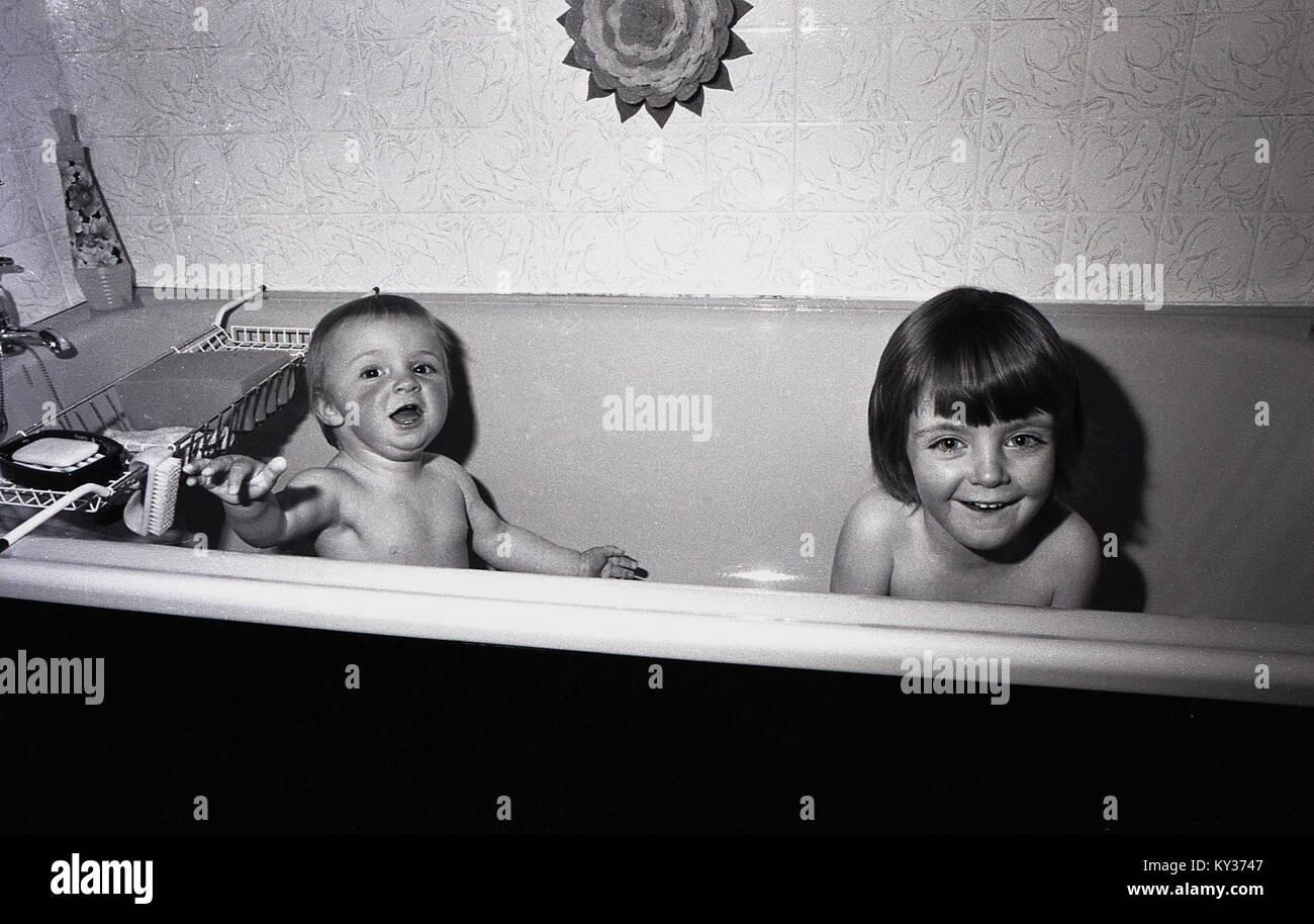 1972, historical, two happy young children enjoying bathtime together, England, UK. - Stock Image