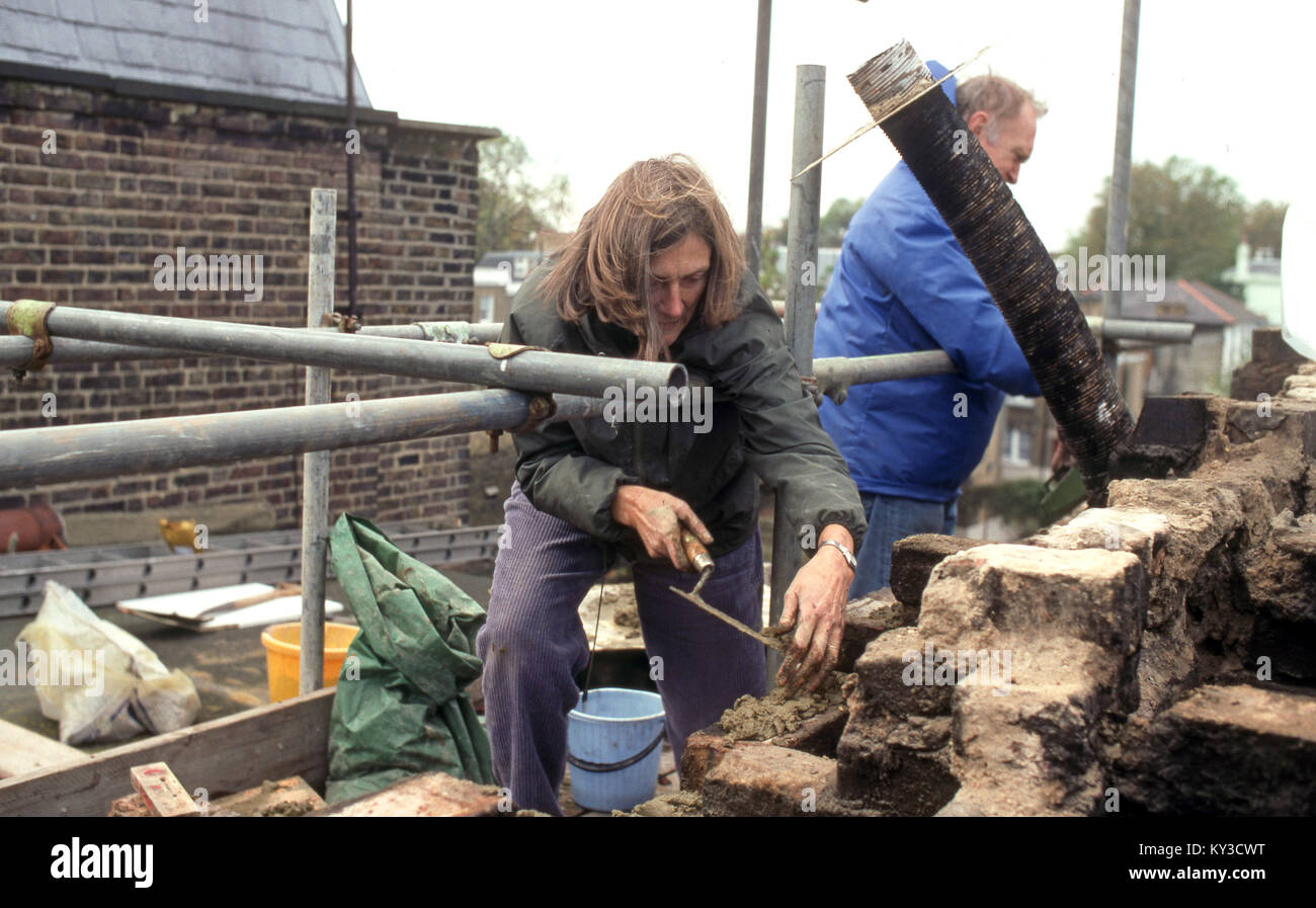 Husband and wife doing repair work on an exterior  wall of their house - Stock Image