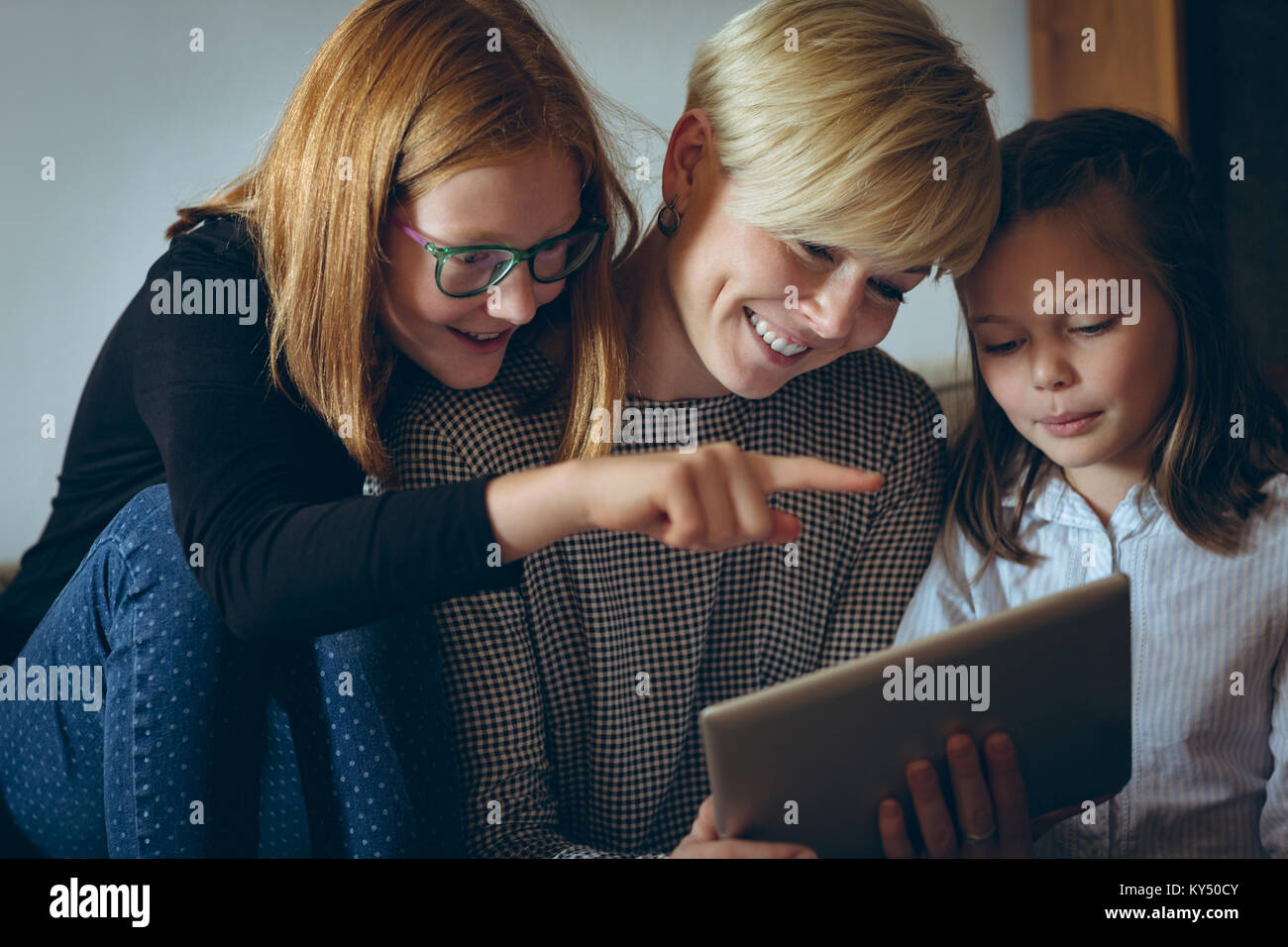 Mother and her kids using digital tablet at home - Stock Image