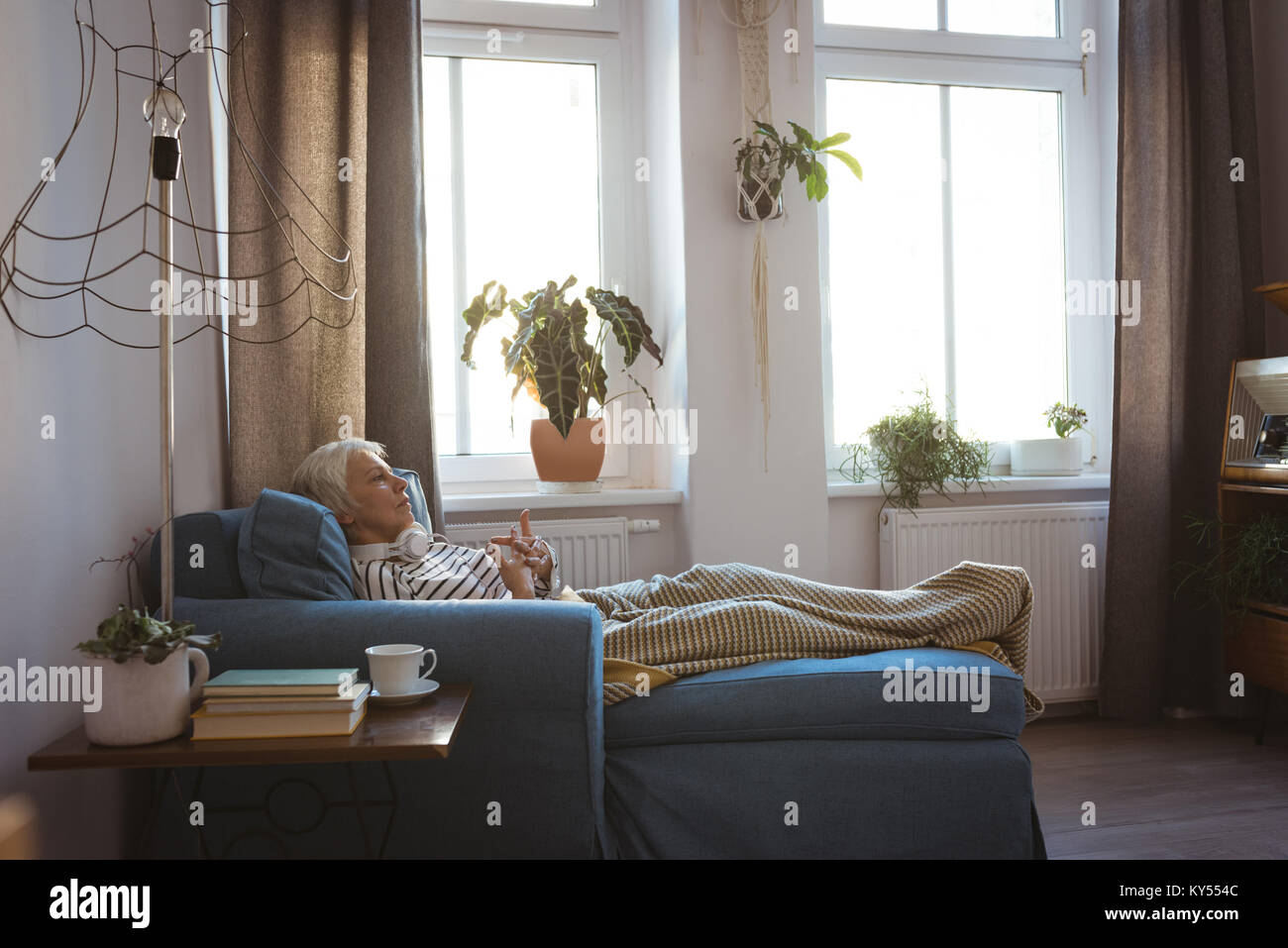 Senior woman relaxing on sofa in living room at home - Stock Image