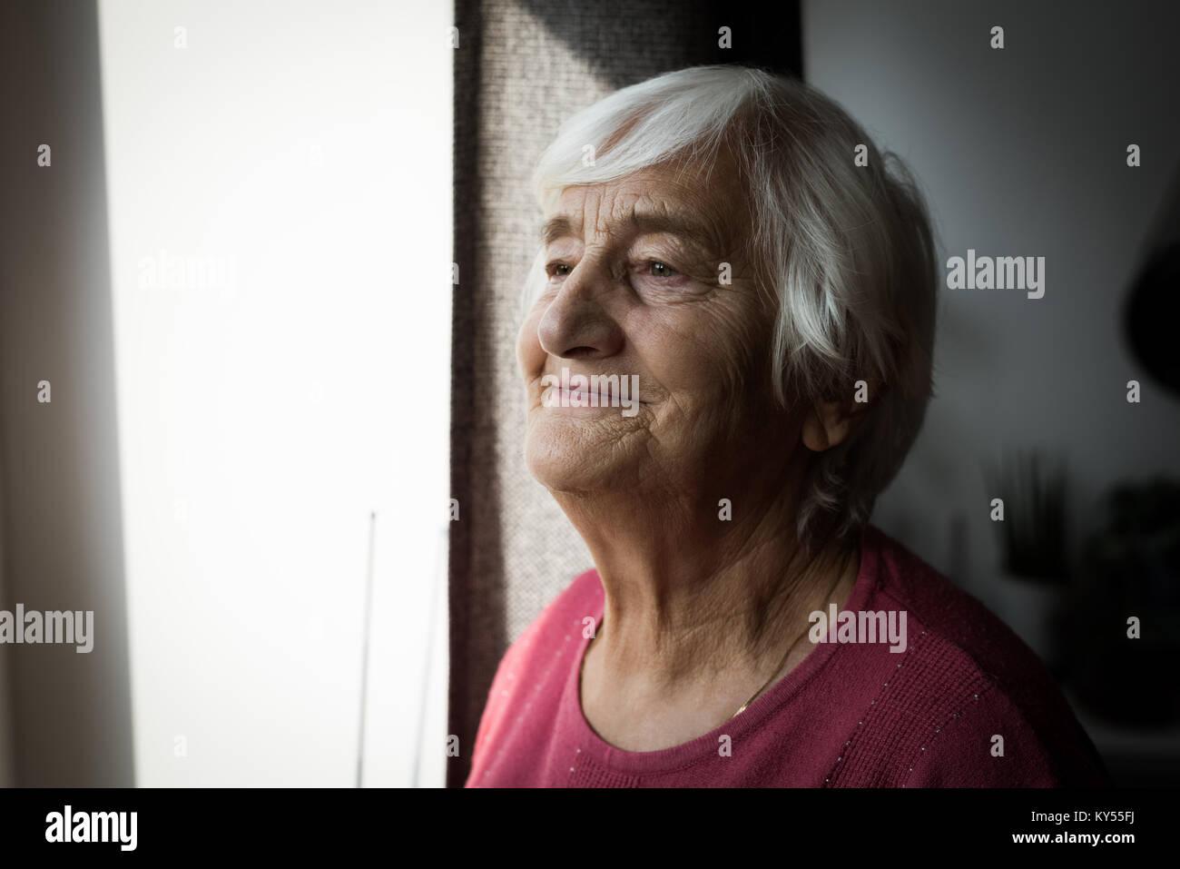 Senior woman standing near window - Stock Image