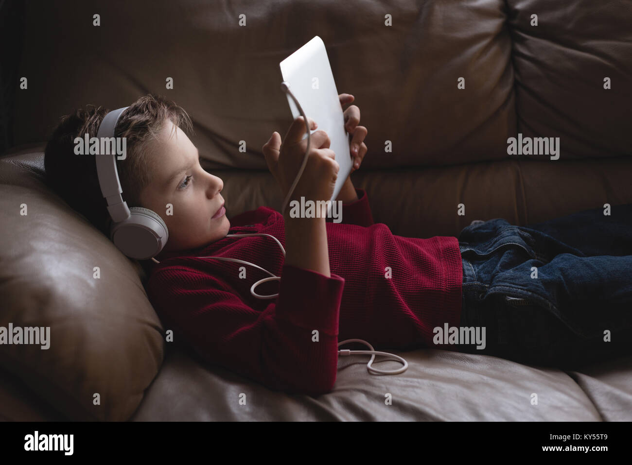 Boy using digital tablet with headphones in living room - Stock Image