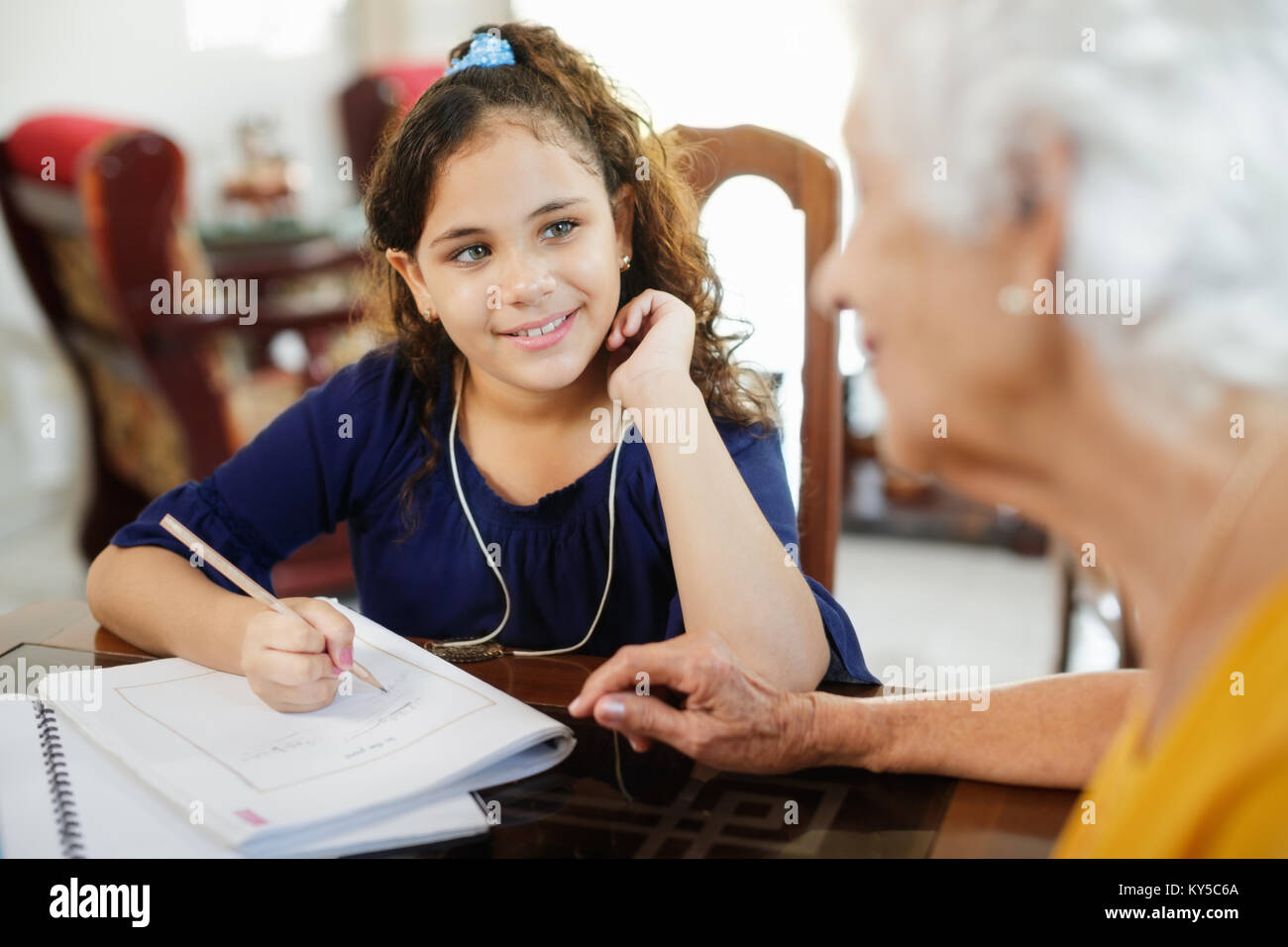 Happy little girl doing school homework with elderly woman at home. Family relationship with grandmother and granddaughter. - Stock Image