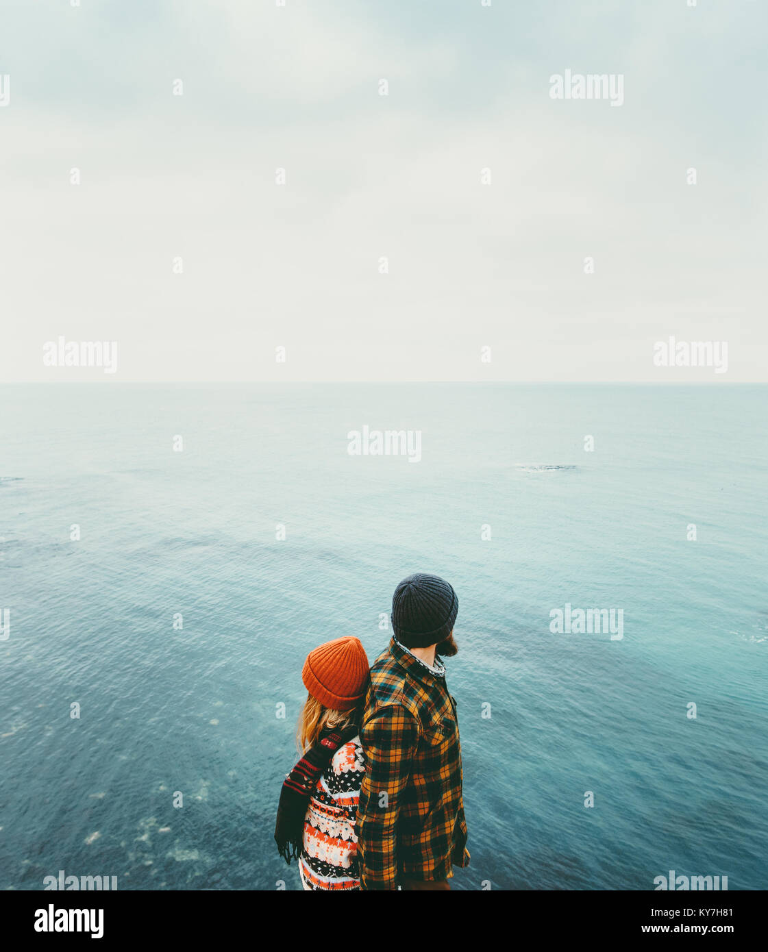 Couple in love Man and Woman back to back standing above sea Traveling together happy emotions Lifestyle concept. - Stock Image