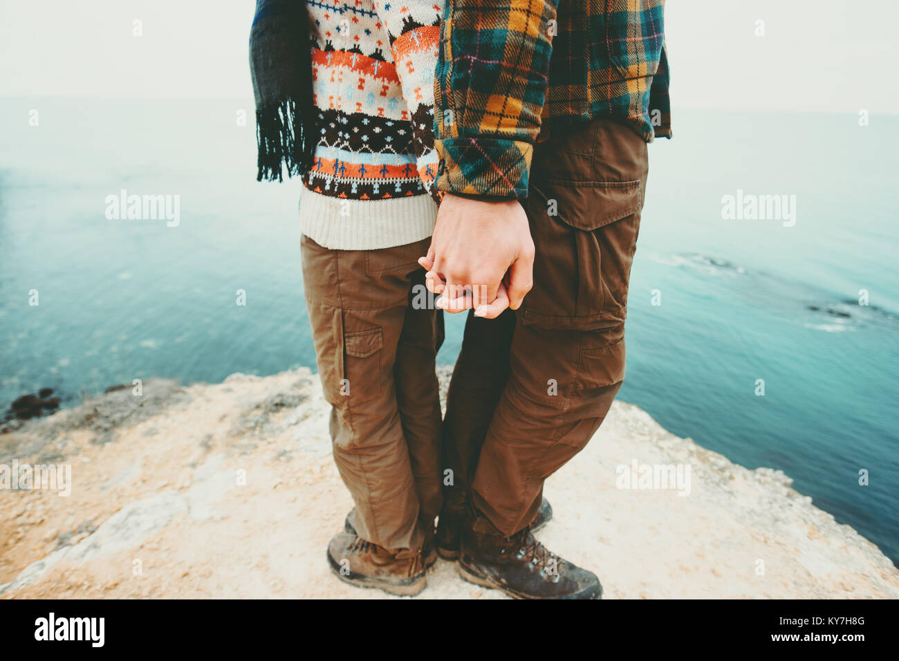 Couple Man and Woman holding hands standing on cliff above sea landscape Love and Travel happy emotions Lifestyle - Stock Image