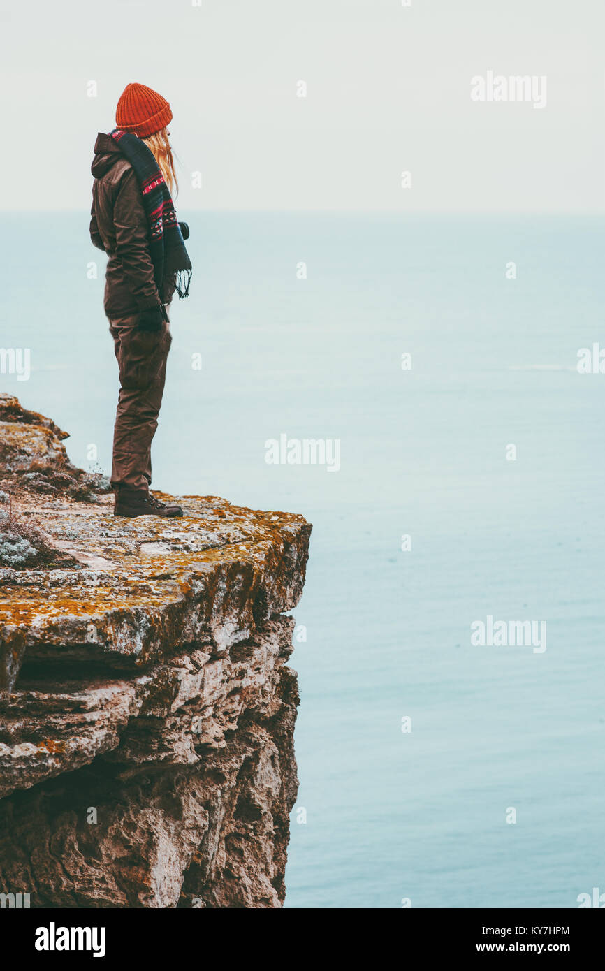 Woman alone standing on cliff edge above sea Travel Lifestyle concept Solitude melancholy emotions harmony with - Stock Image