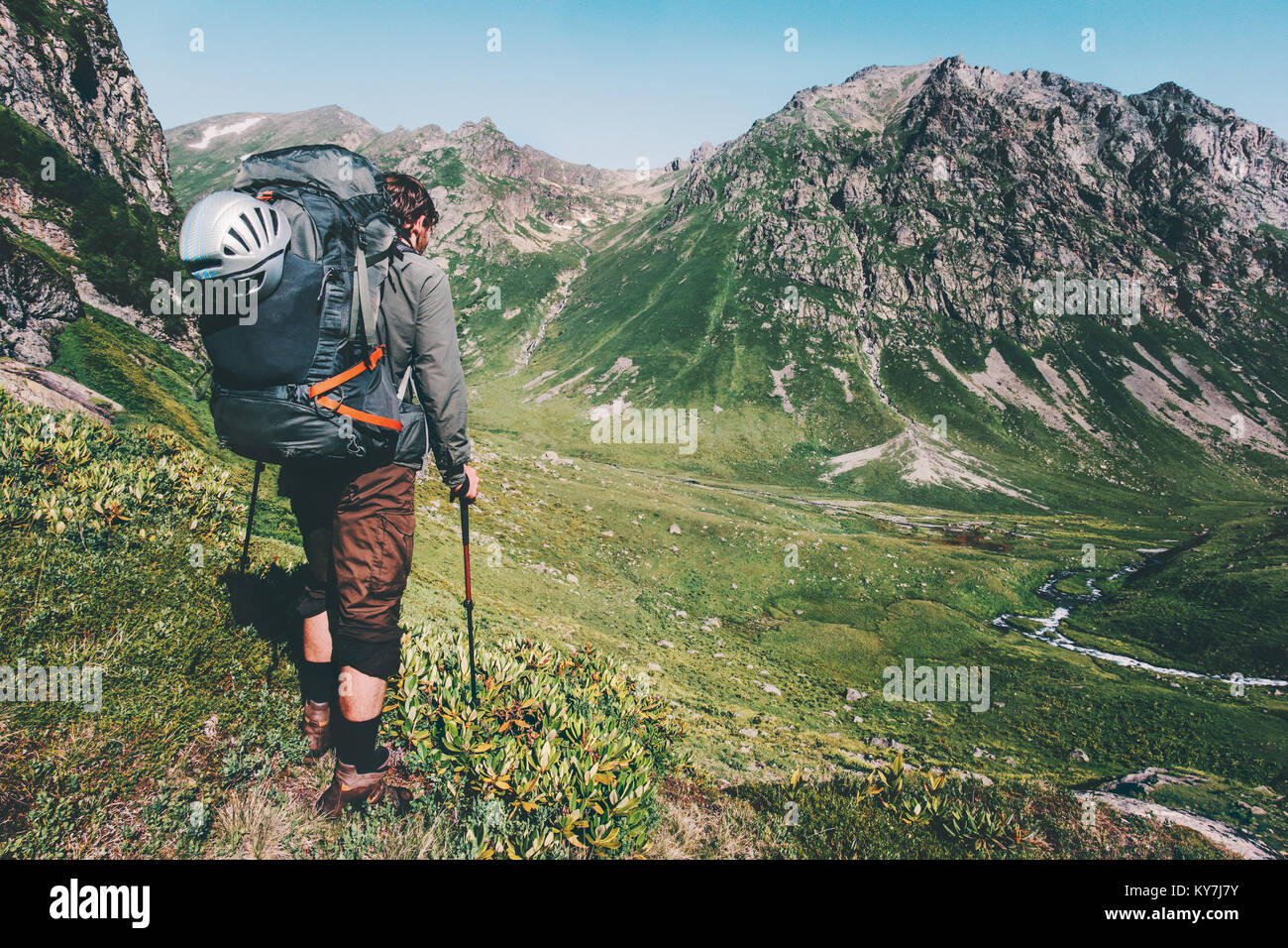 Man hiking at mountains with heavy big backpack Travel Lifestyle wanderlust adventure concept summer active vacations - Stock Image