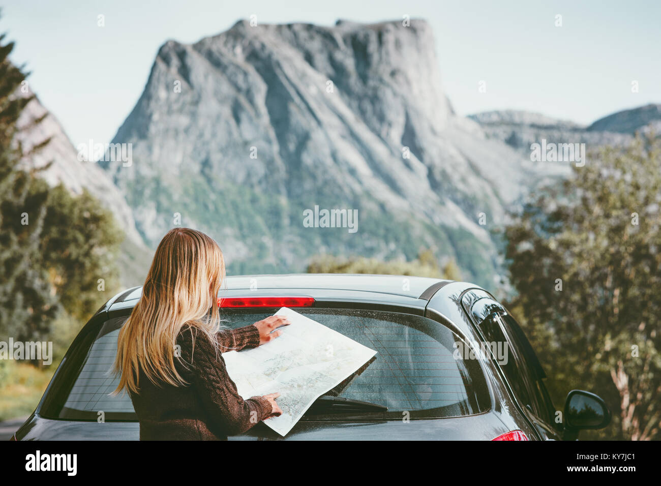 Woman traveling by car on road trip with map planning route Lifestyle concept adventure vacations outdoor - Stock Image