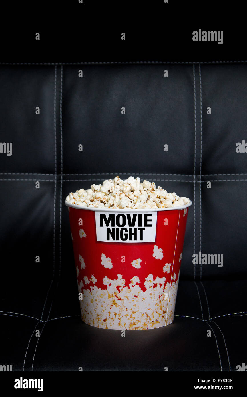 Closeup Of A Popcorn Box On A Black Leather Couch With Black Stock